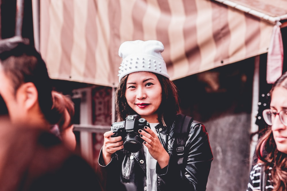 woman in black leather jacket holding DSLR camera