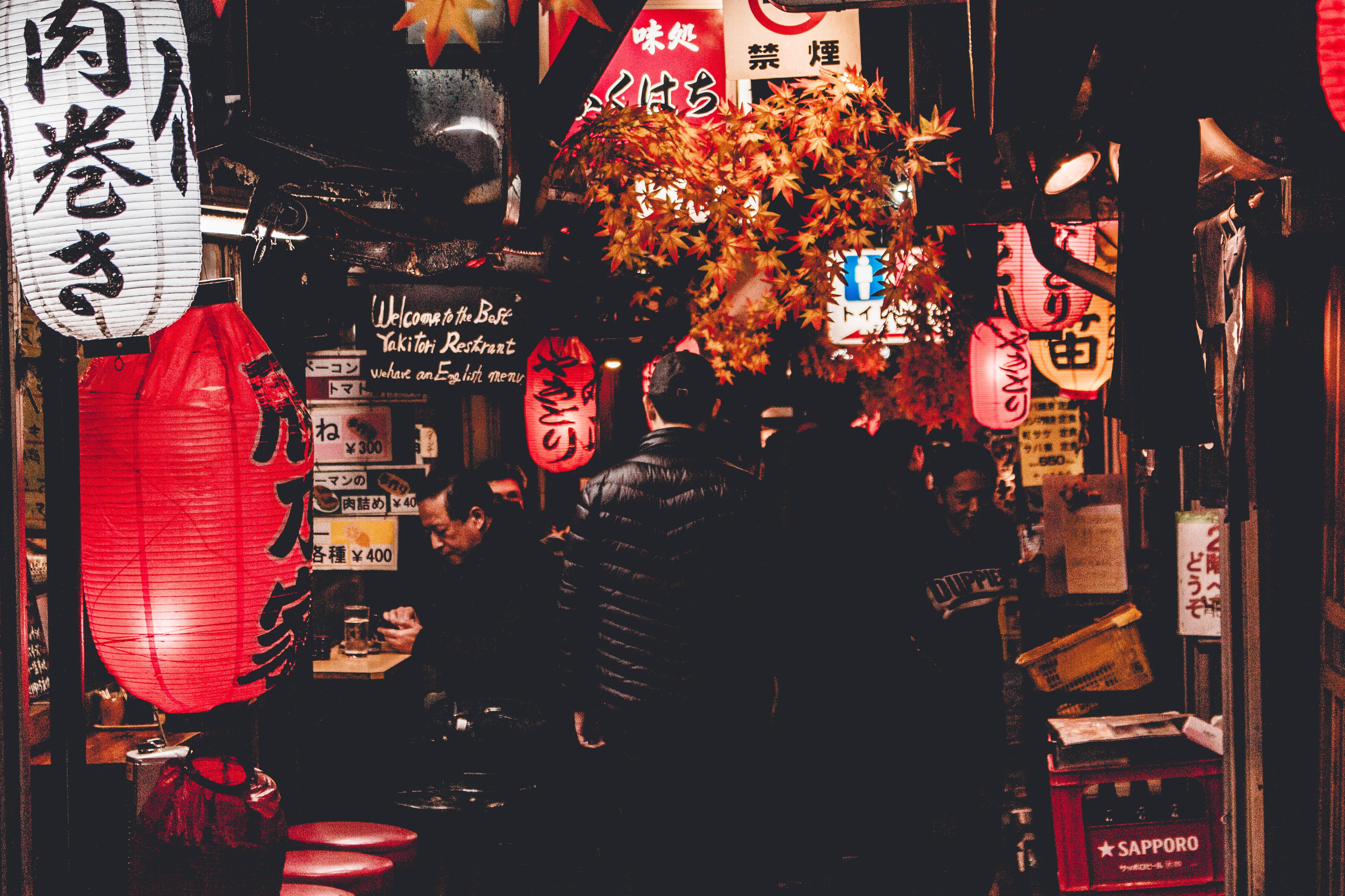 People walking past stalls in a narrow market alley in an Asian City at night