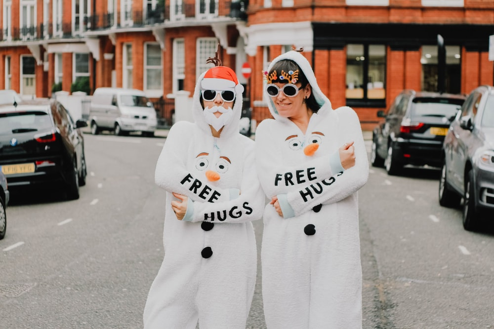 two women wearing coveralls standing next to each other