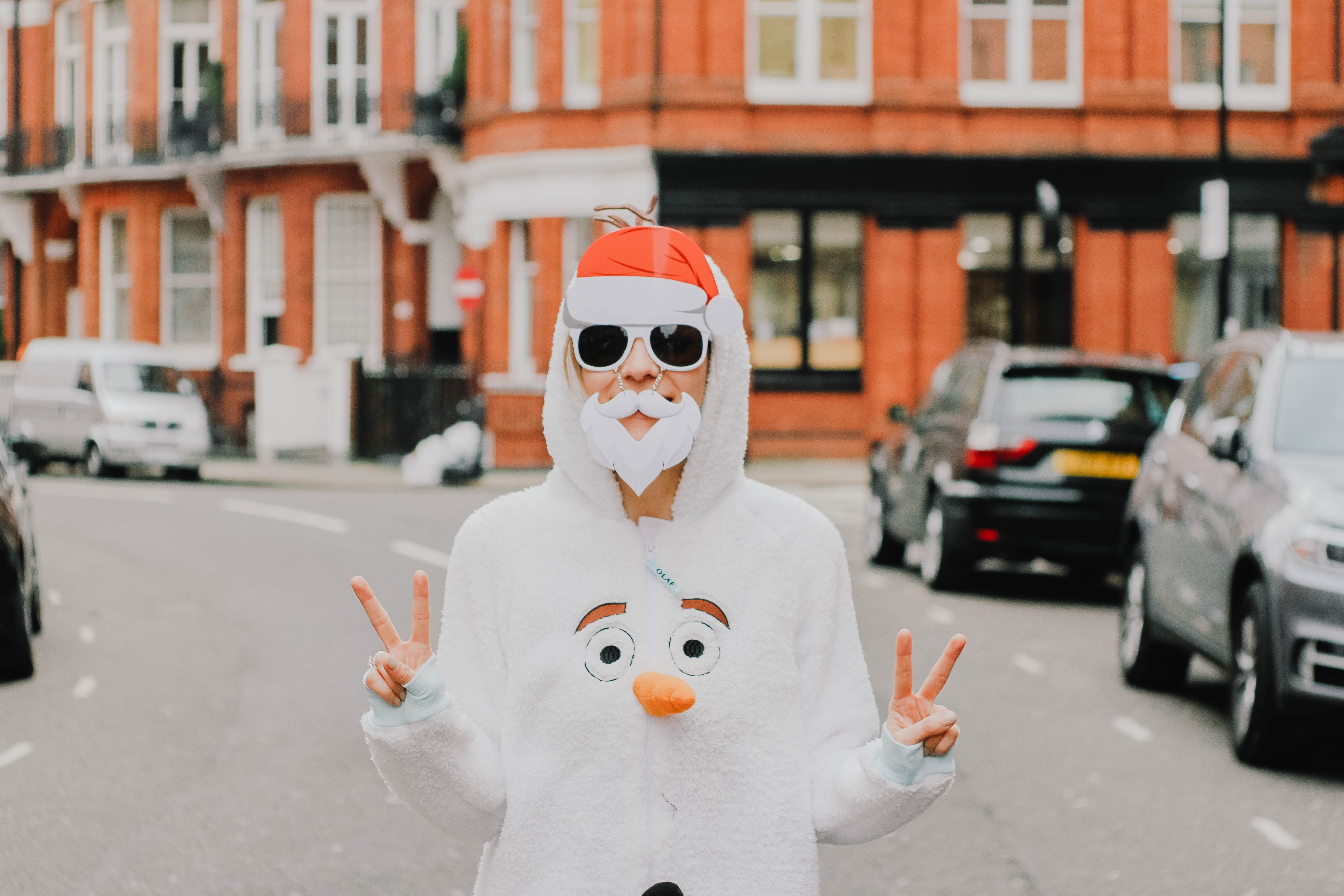 A person wearing a fake white beard and Santa hat, with a jumper suit that features a snowman's face on the chest.