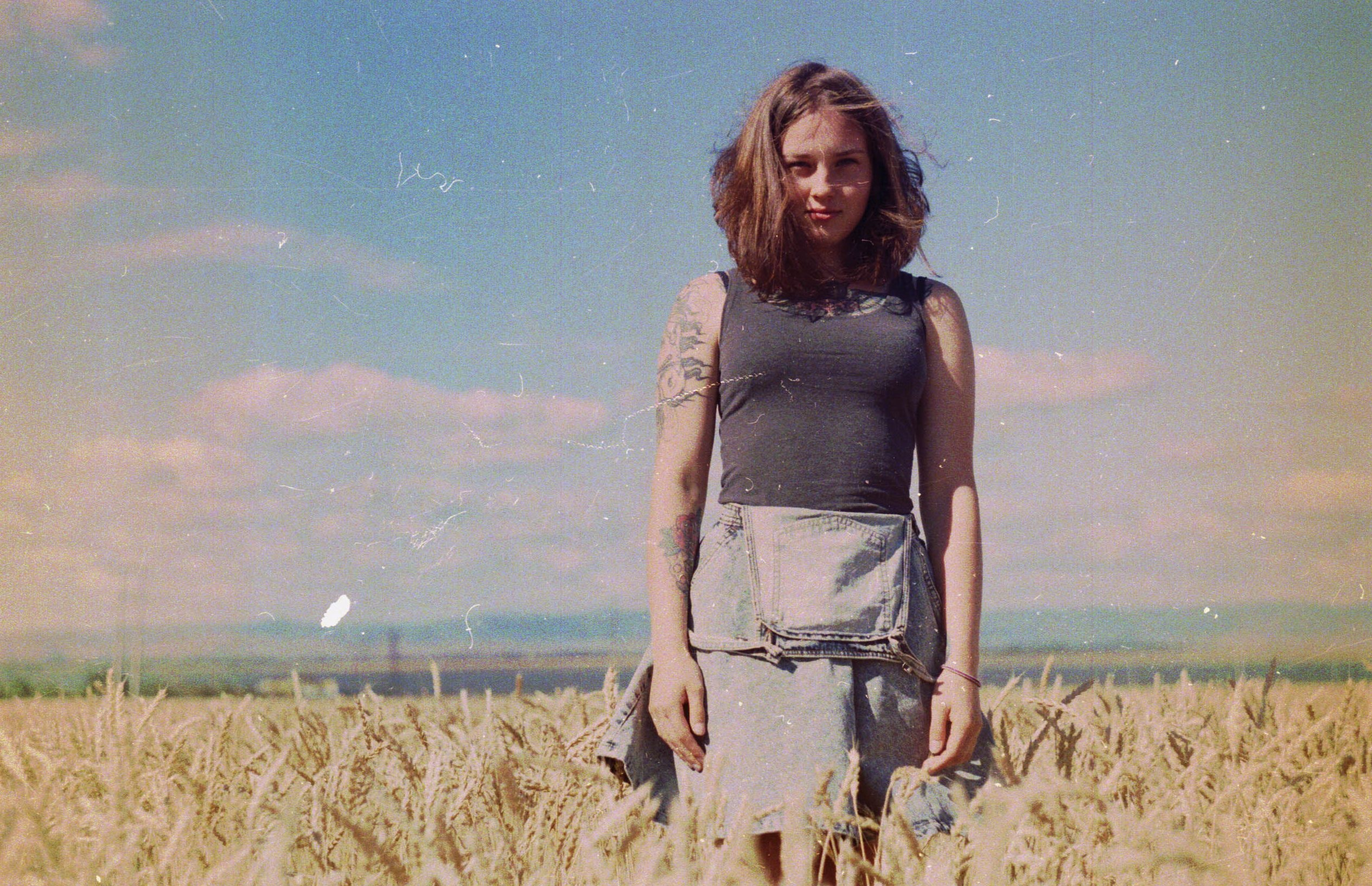 A tattooed woman in a denim skirt stands in a wheat field in the Ural Mountains
