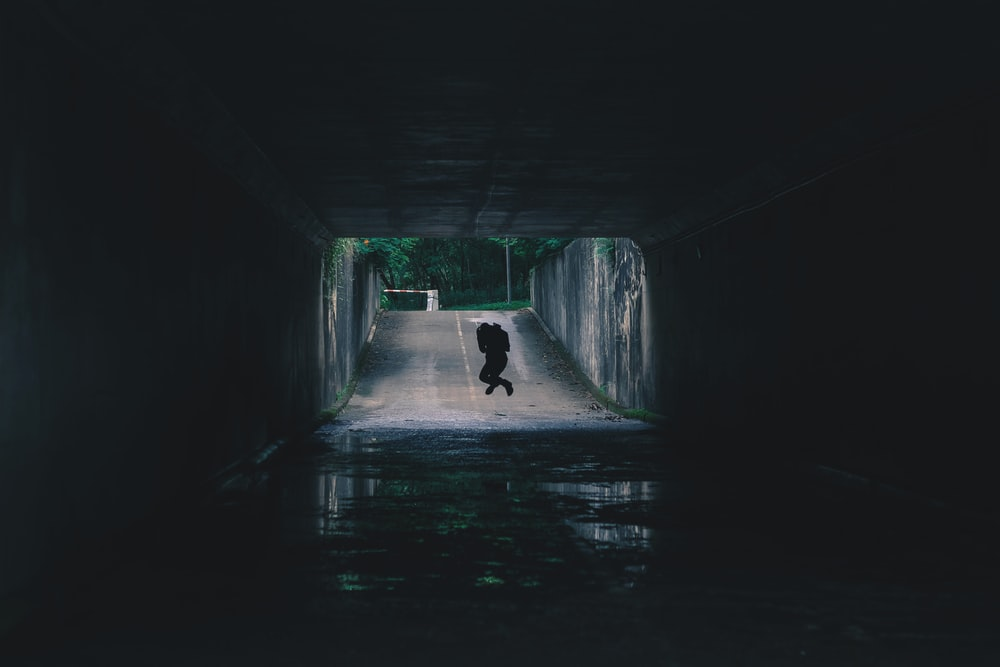 silhouette of person inside tunnel