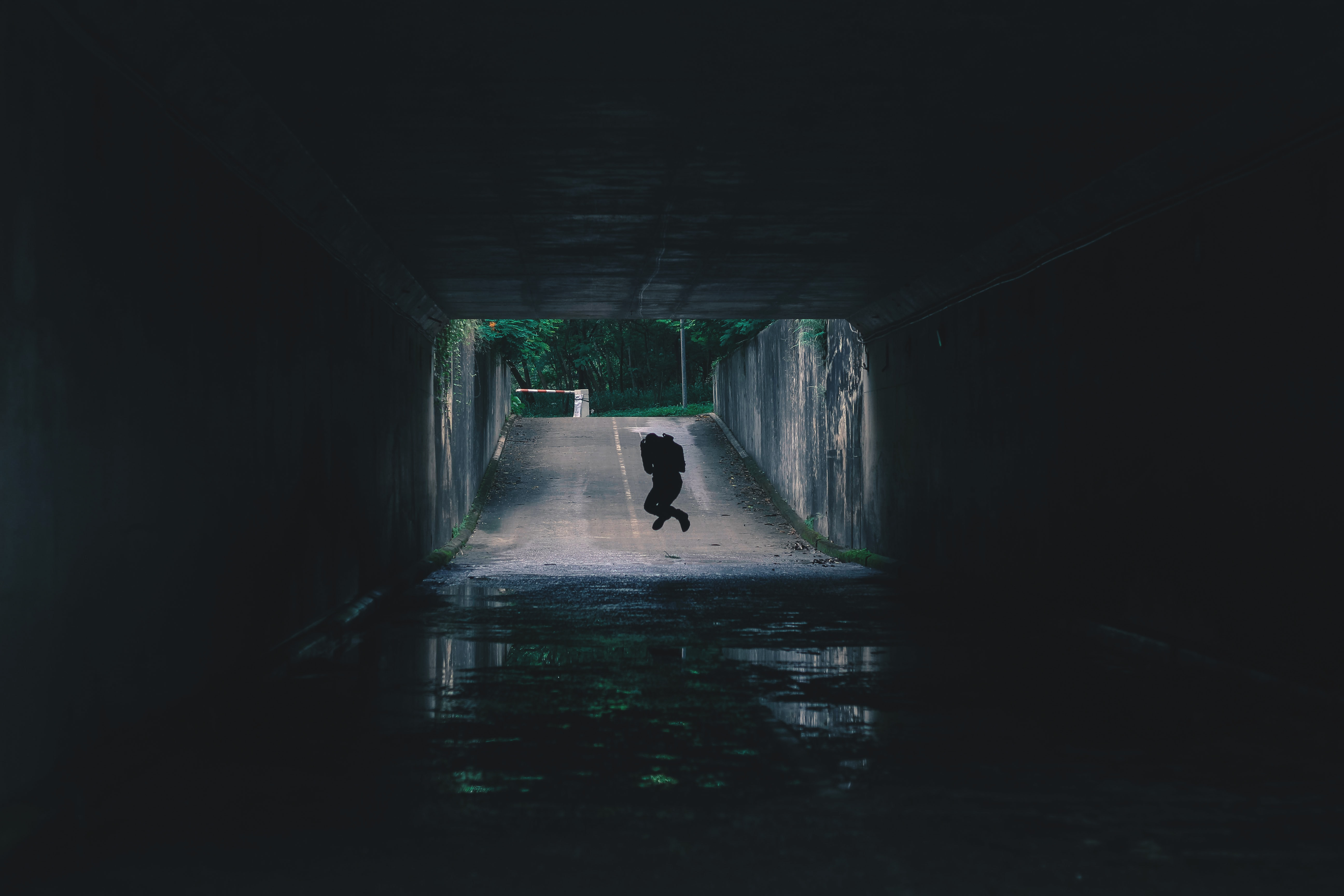 A silhouette of a person hovering above ground in a dark wet tunnel