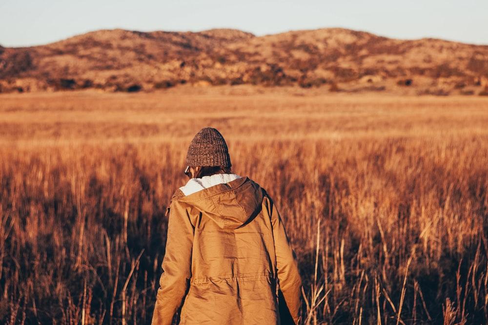 person wearing jacket walking in brown grass field