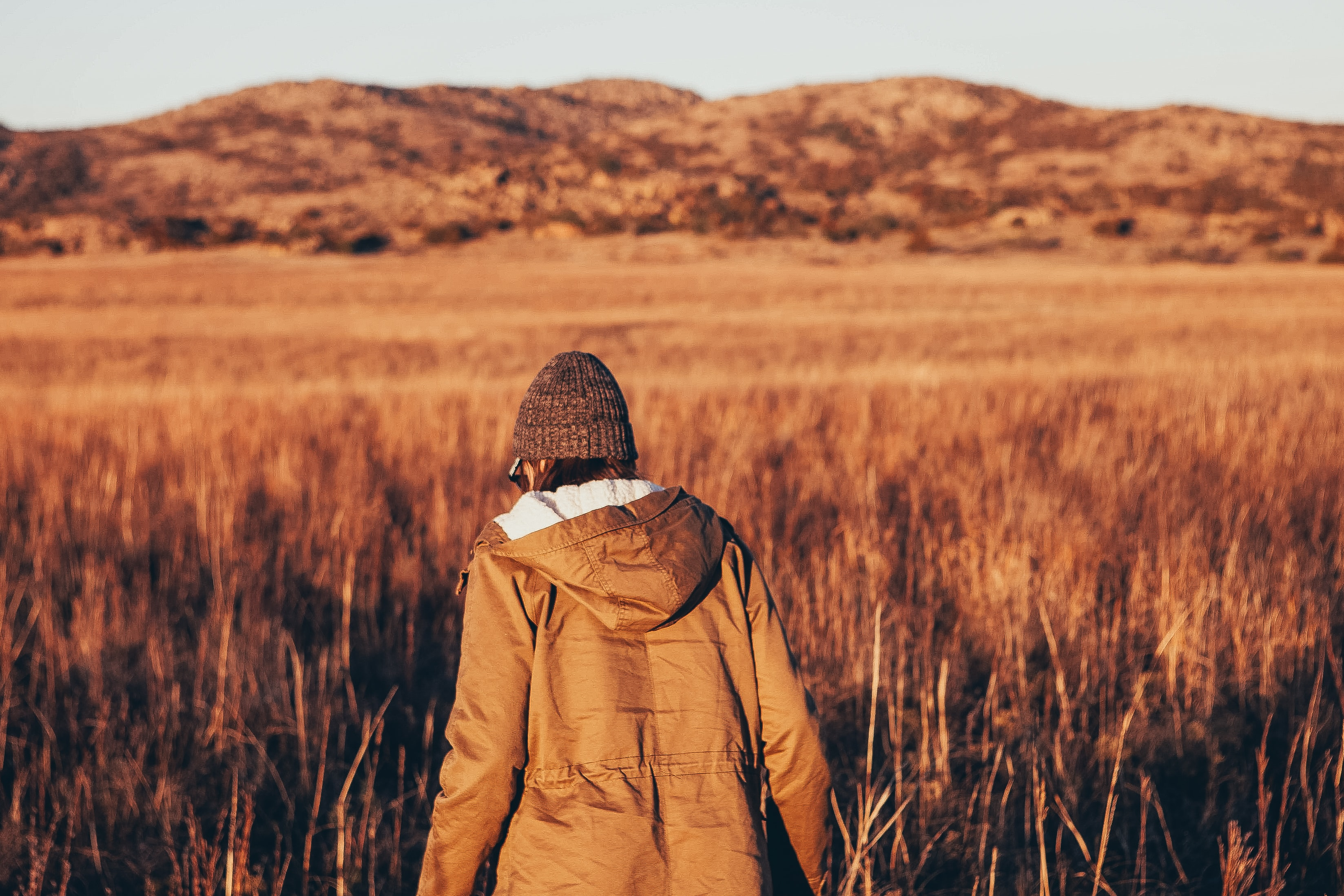 A person in a coat faces away while hiking in a field by the Wichita Mountains