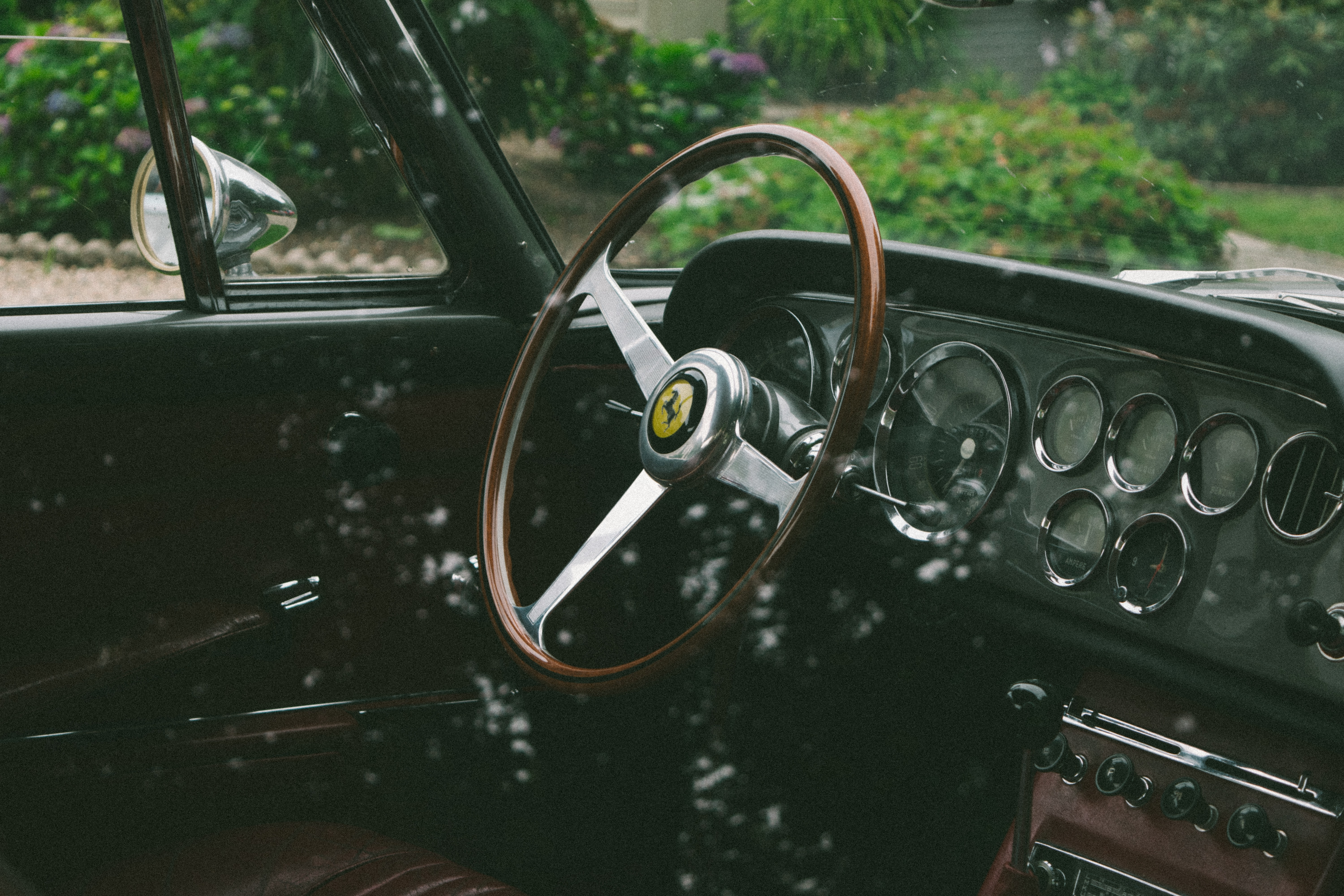 Vintage steering wheel and dashboard in classic car with bushes in the background