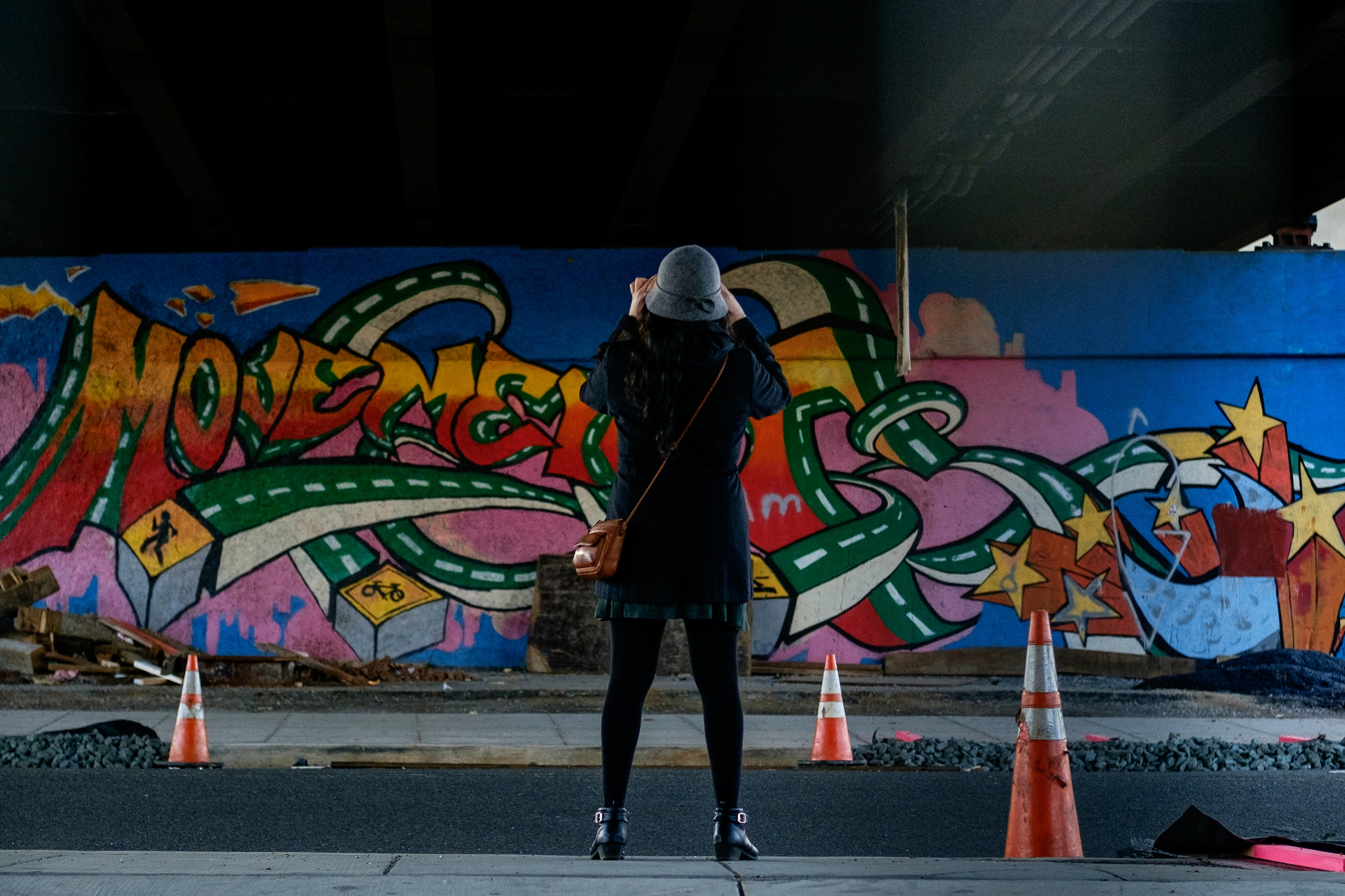 Woman in felt hat with traffic cones viewing colorful graffiti street art, Rhode Island Avenue Northwest