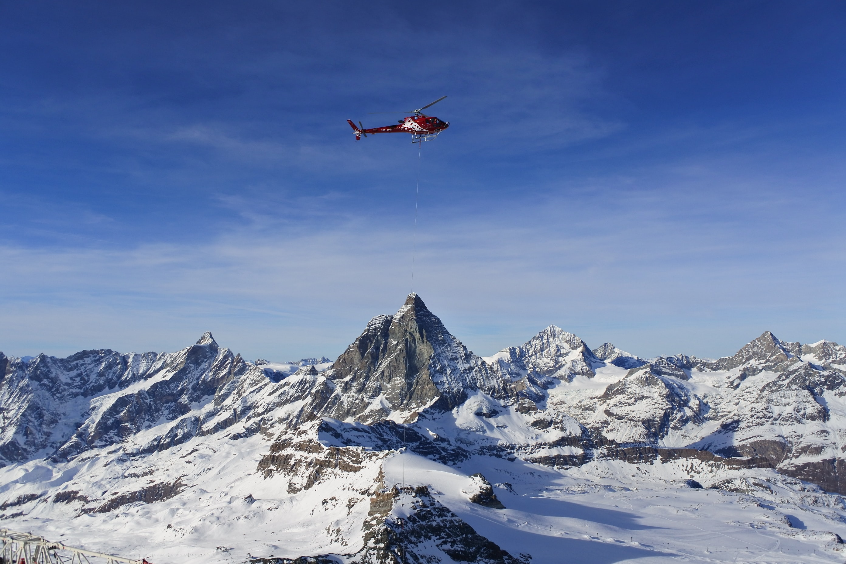 A rescue helicopter with a rescue hoist in the air above snowy mountains