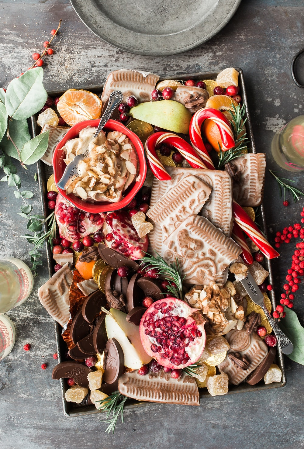 variety of sliced fruits, cookies, and chocolates on gray steel tray