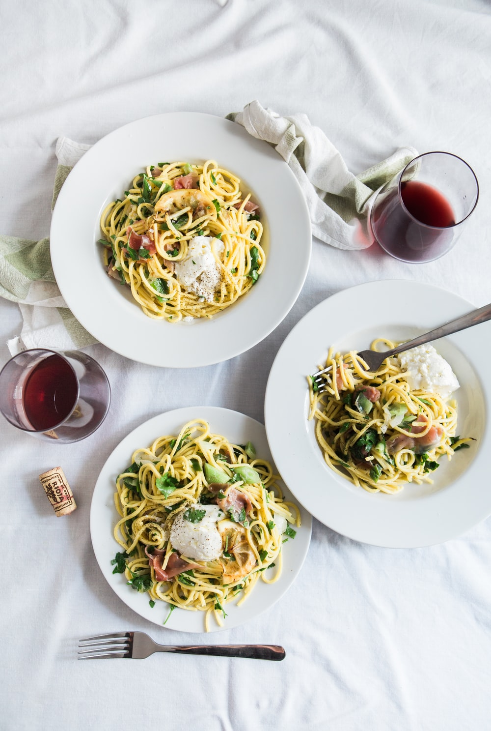 An overhead shot of two glasses of red wine next to three plates of pasta with pancetta on a white tablecloth