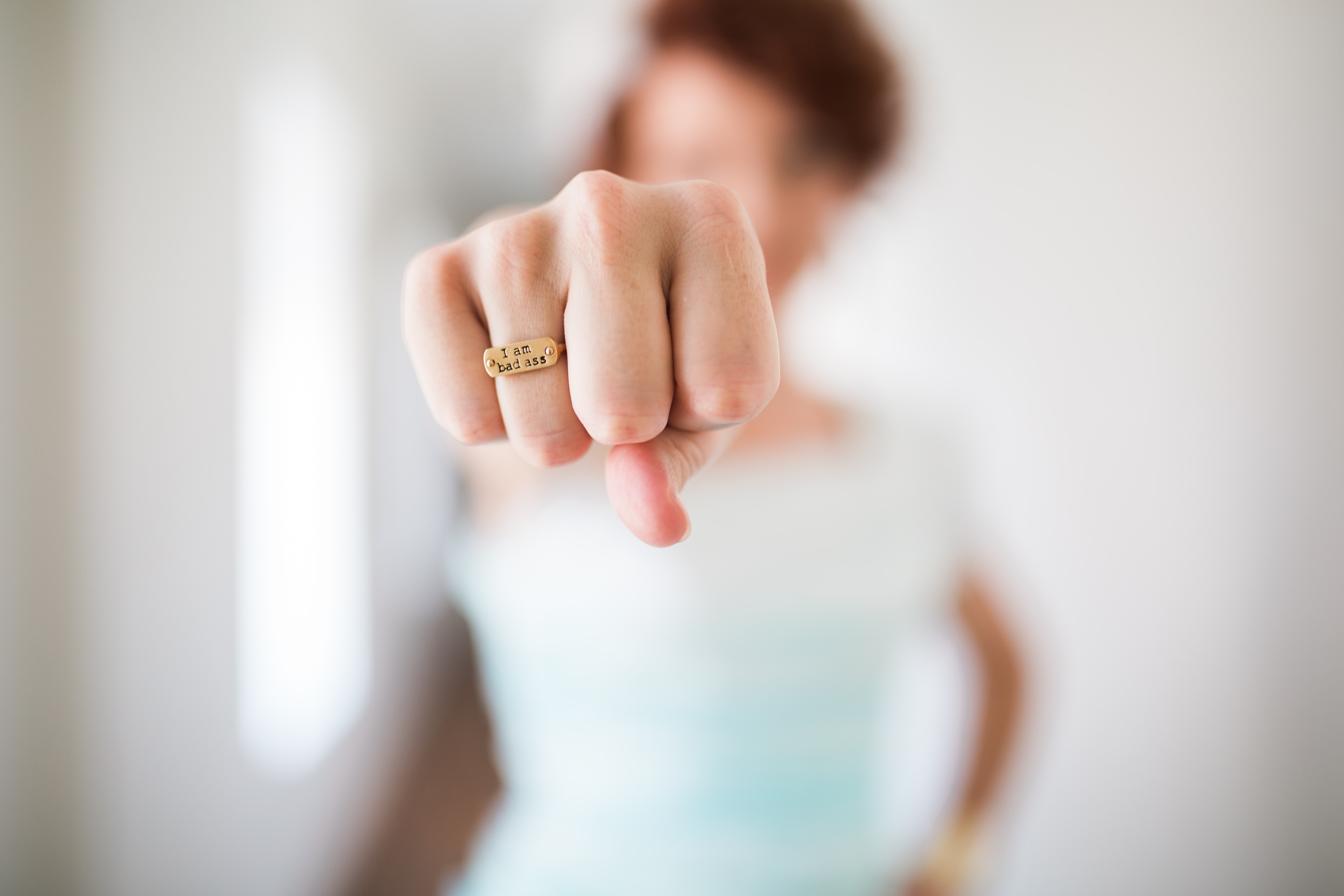"A person's clenched fist with an engraved ring with the phrase ""I am badass"""