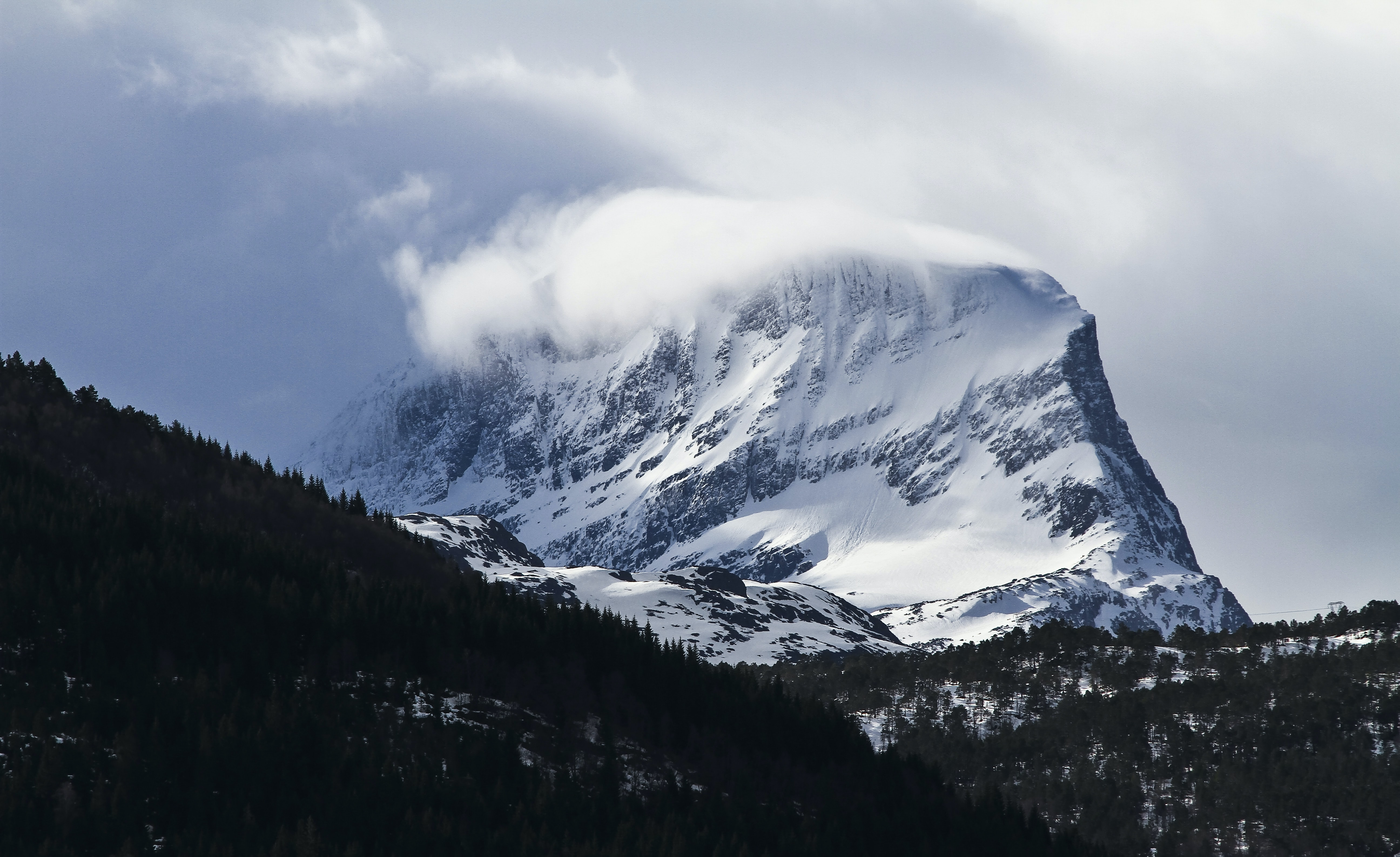 Wind blowing snow off a steep mountain