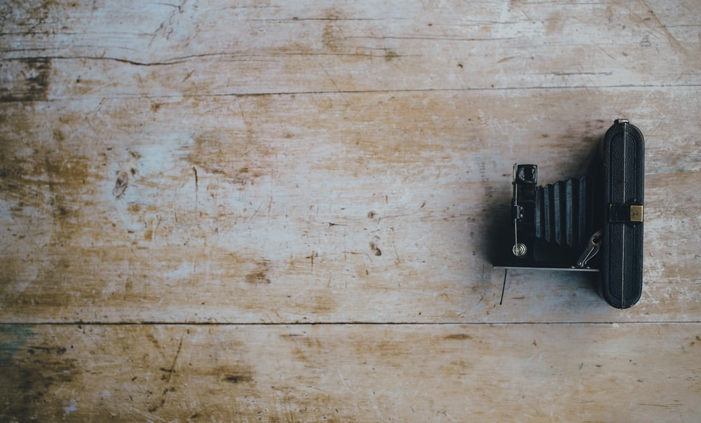 classic black camera on brown wooden surface