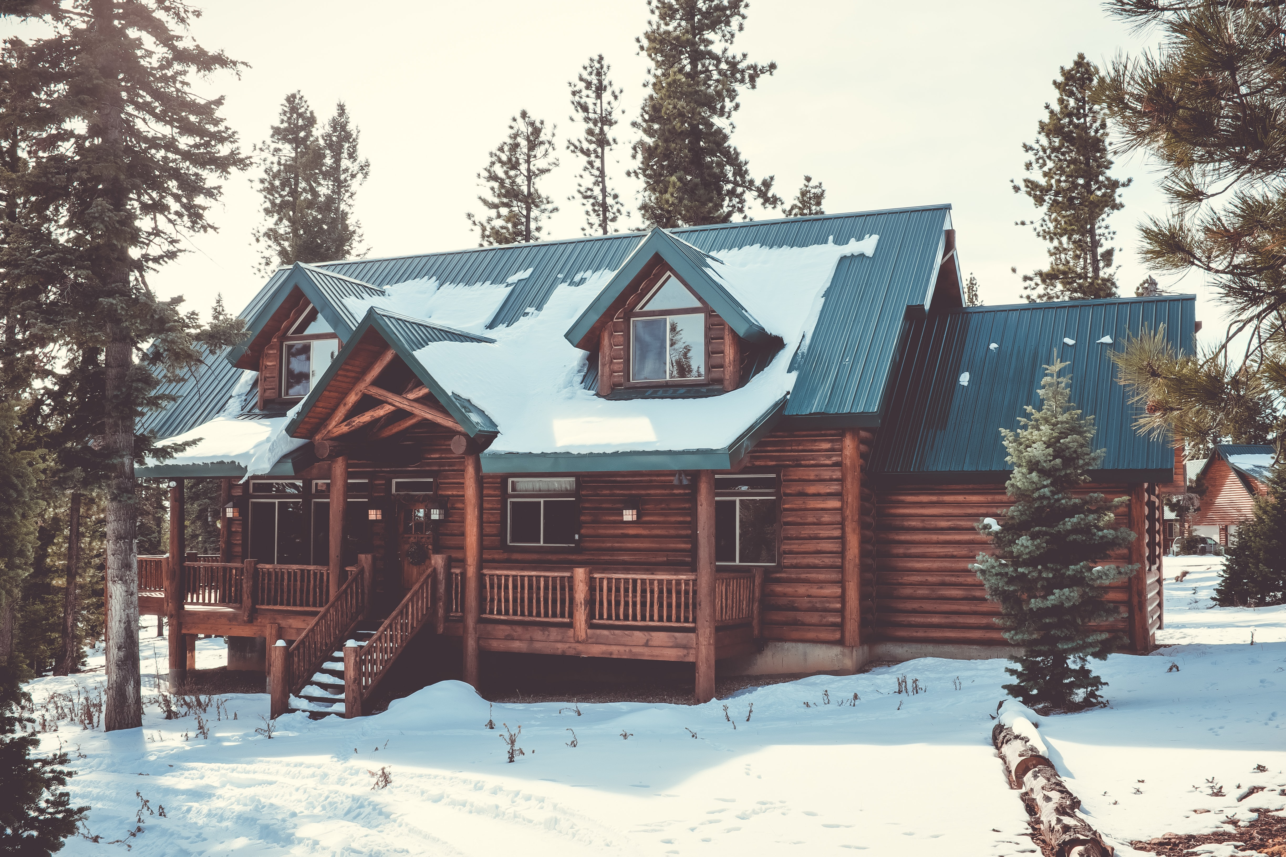 A snow covered log cabin in the forest surrounded by pine trees