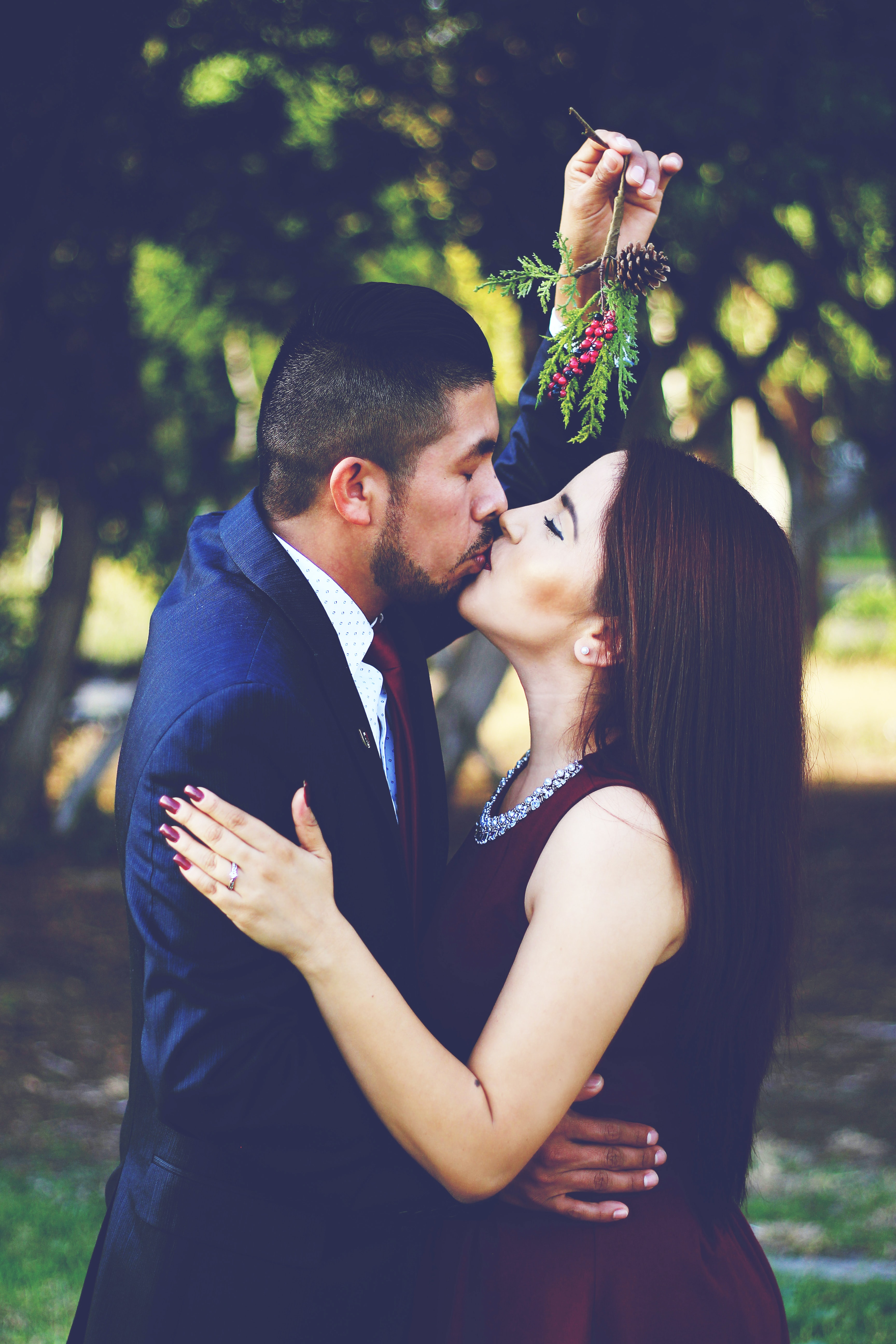 A man and woman in formalwear kiss outdoors while he holds mistletoe over their heads
