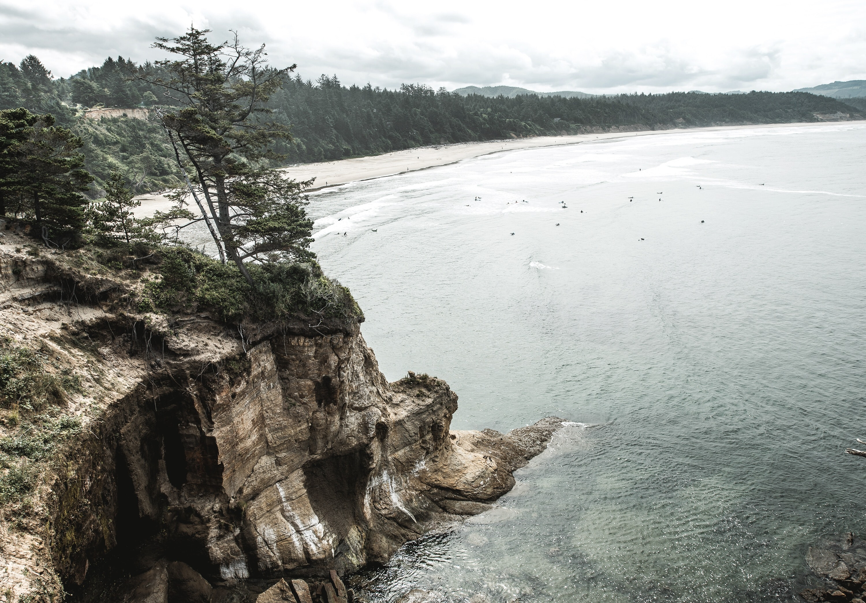 A dramatic shot of a rocky cliff connecting to a wooded shoreline on a body of water