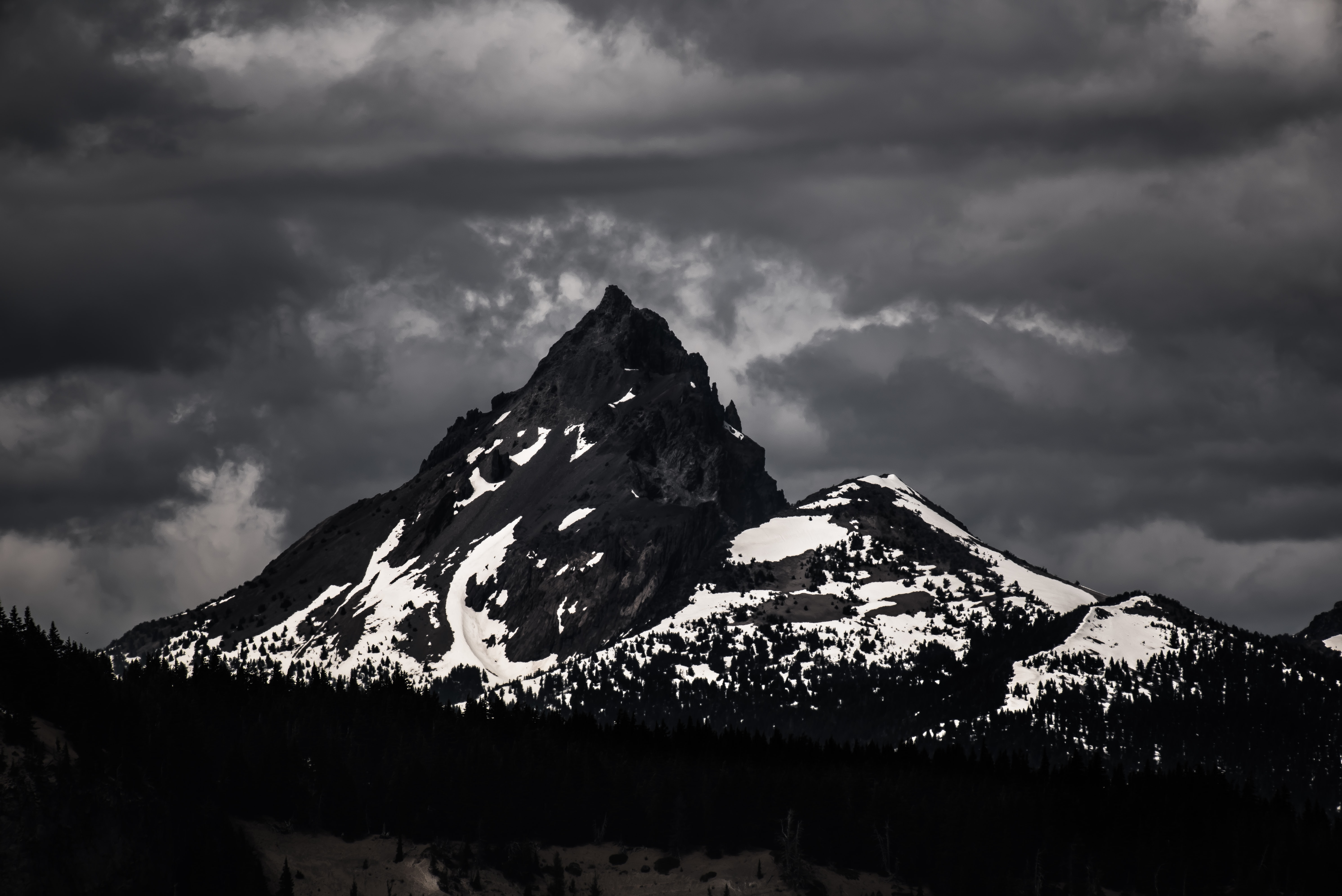 A desaturated shot of a dark mountain covered in patches of white snow under a gray sky