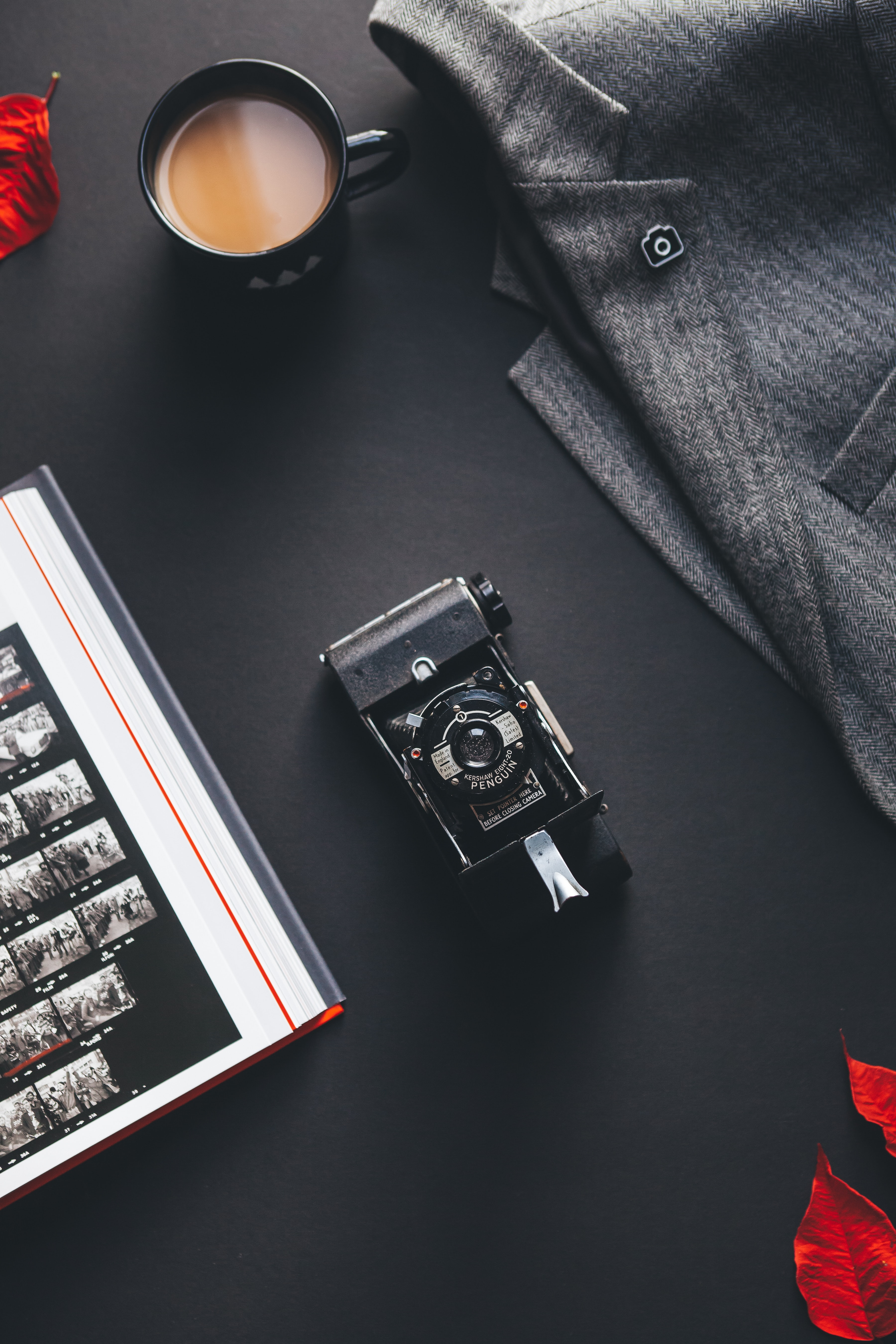 A flatlay of a vintage camera, jacket, Unsplash pin, cup of coffee, contact sheet, and red leaves
