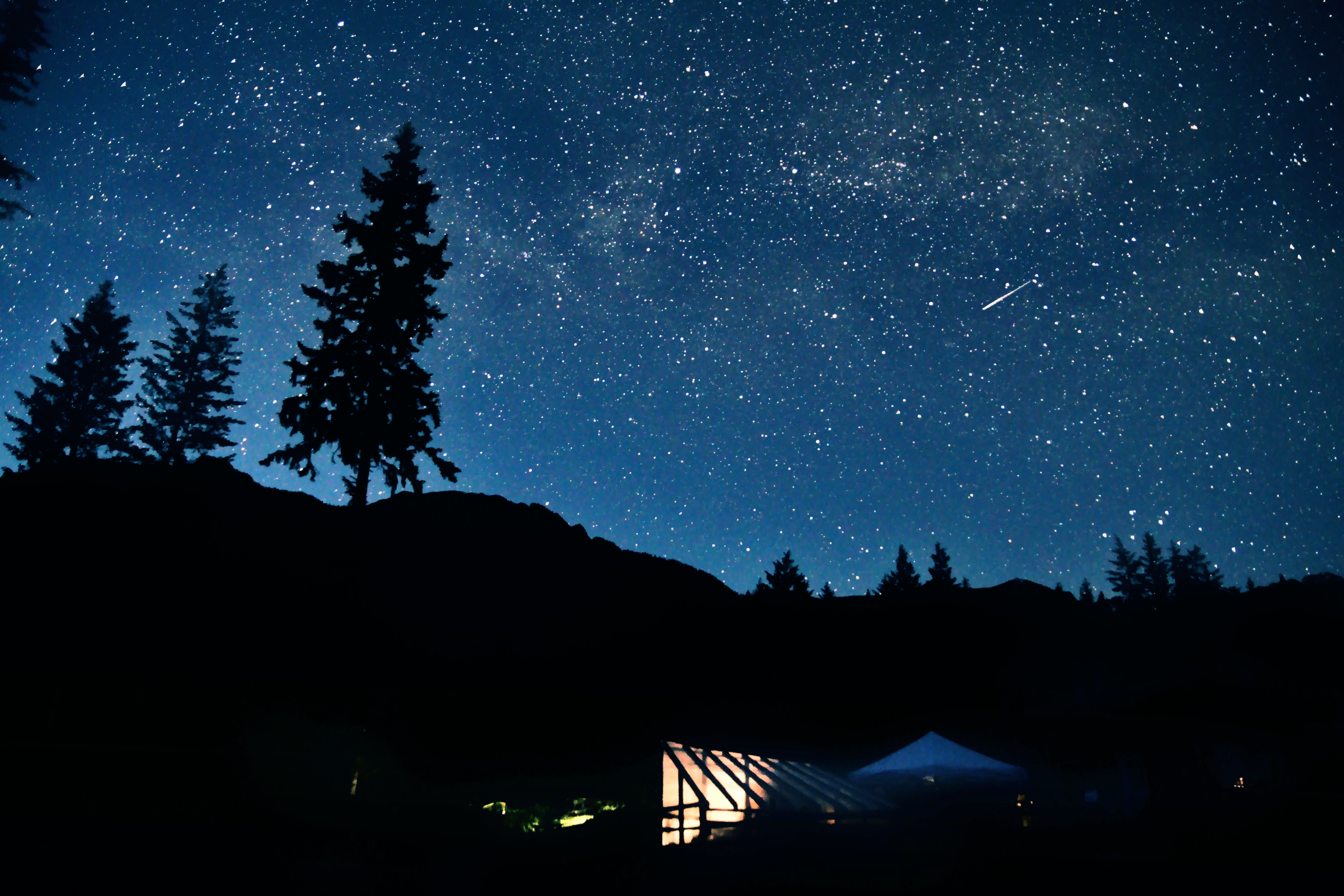 A shooting star travels across the starry night above a lighted tent in Golden.