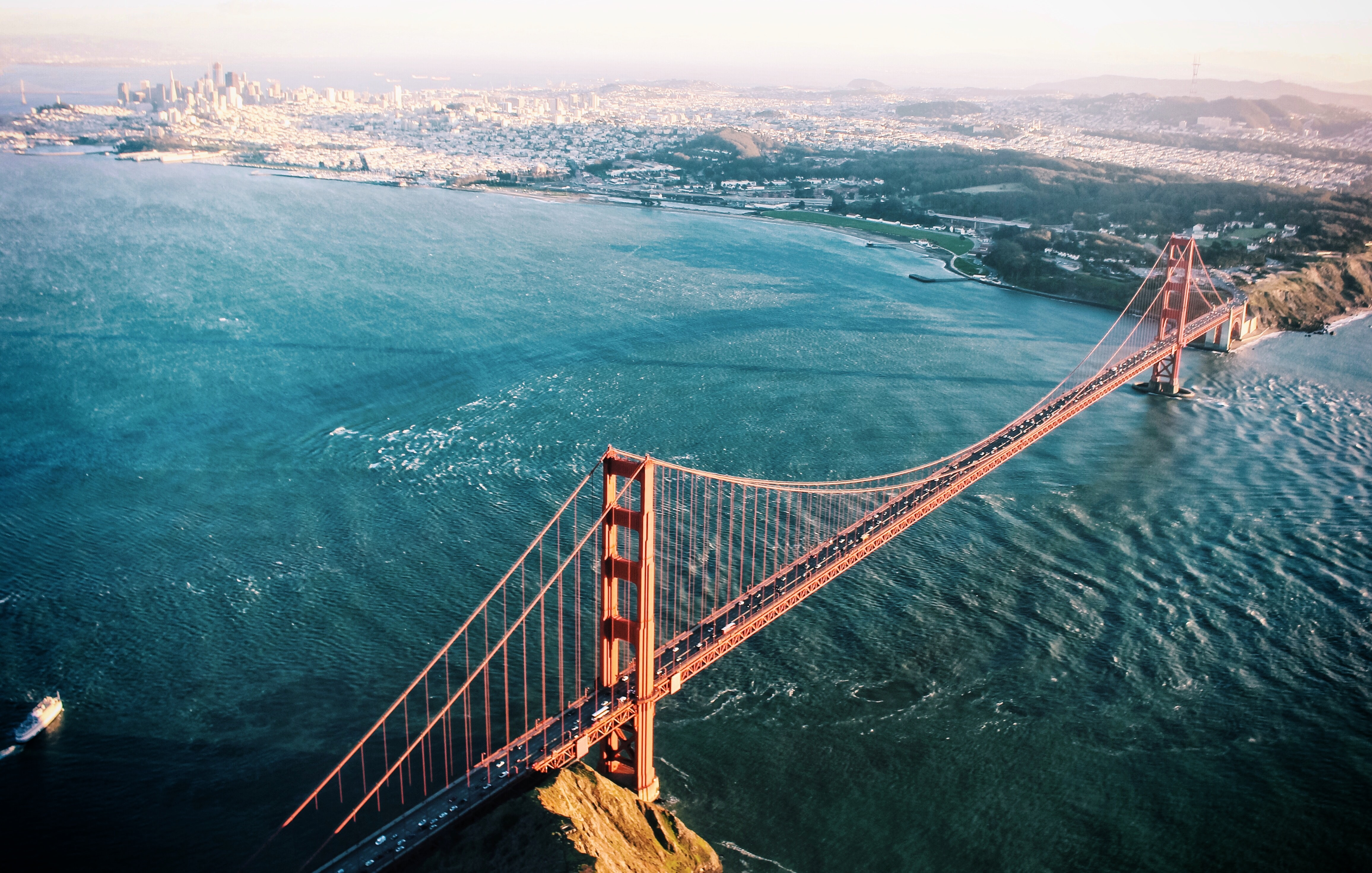 Drone view of San Francisco Golden Gate Bridge over crystal blue water and harbor in background