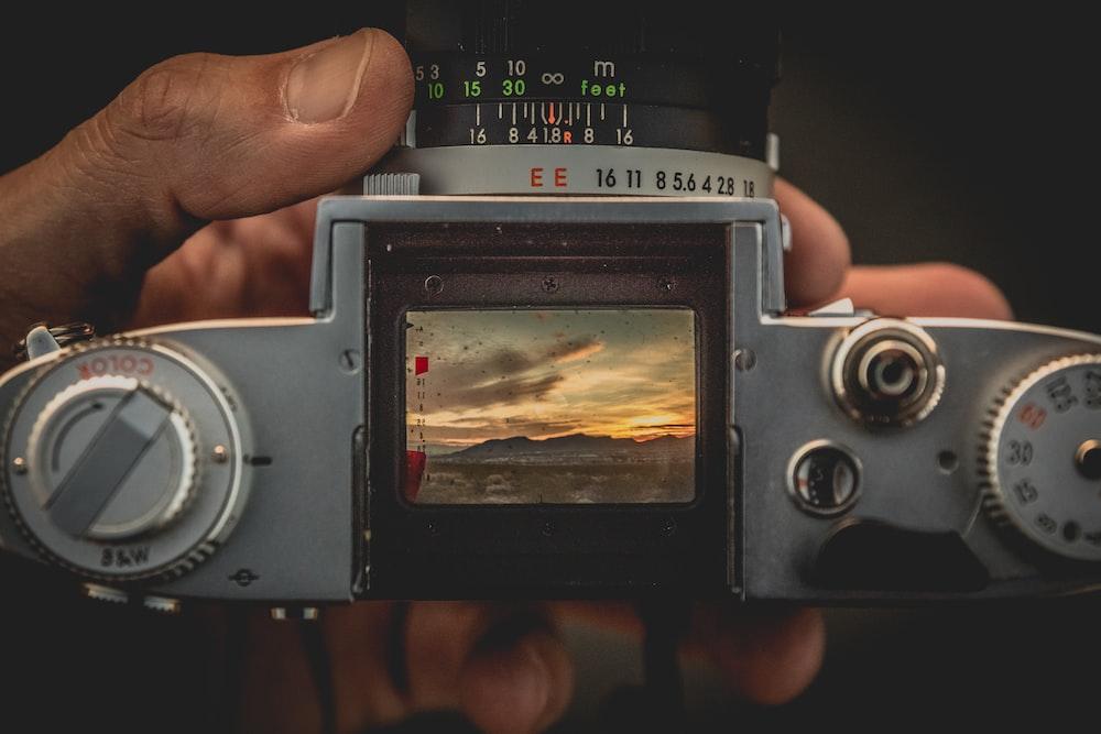 person holding gray film camera
