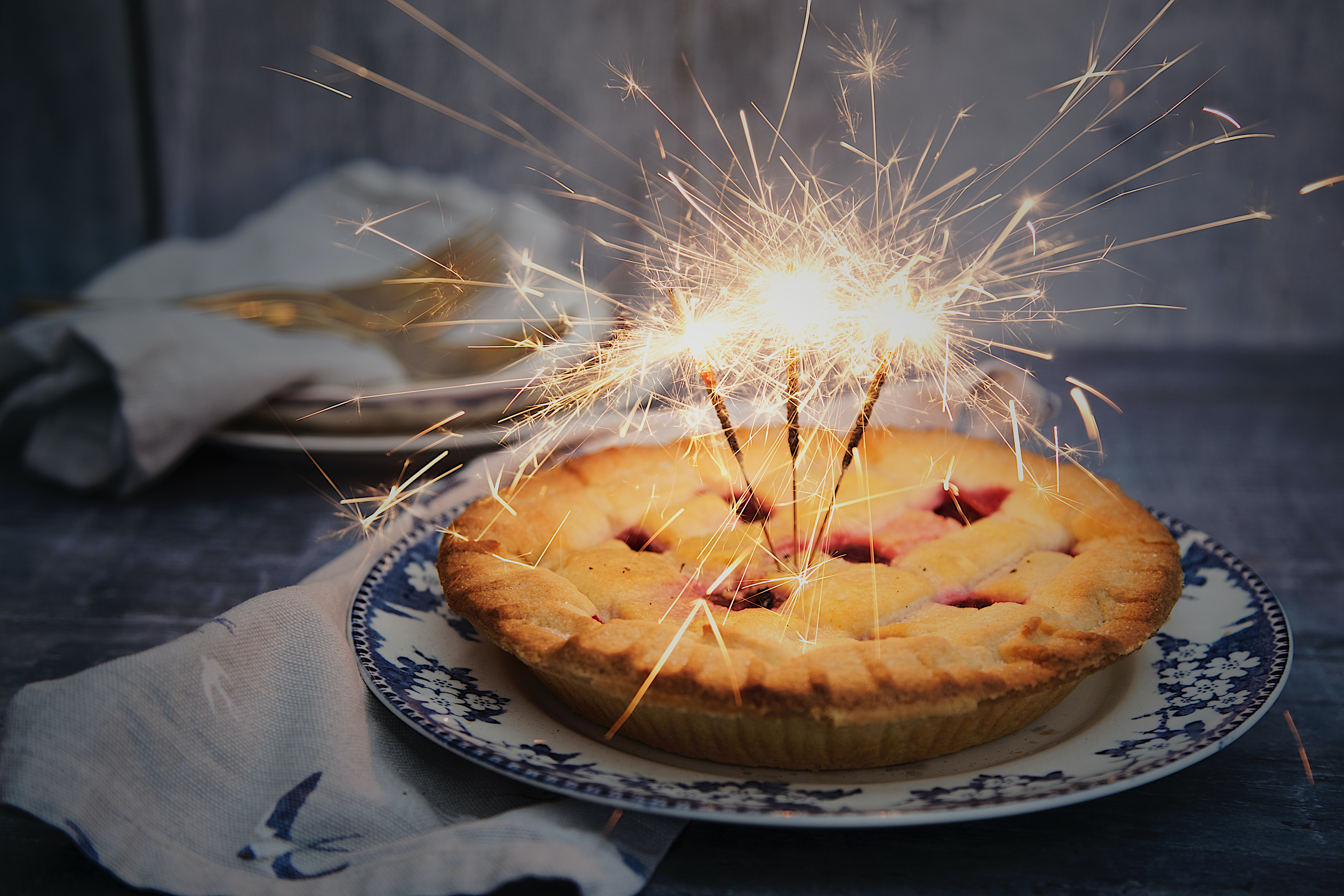 Sparklers lit in a fresh berry pie