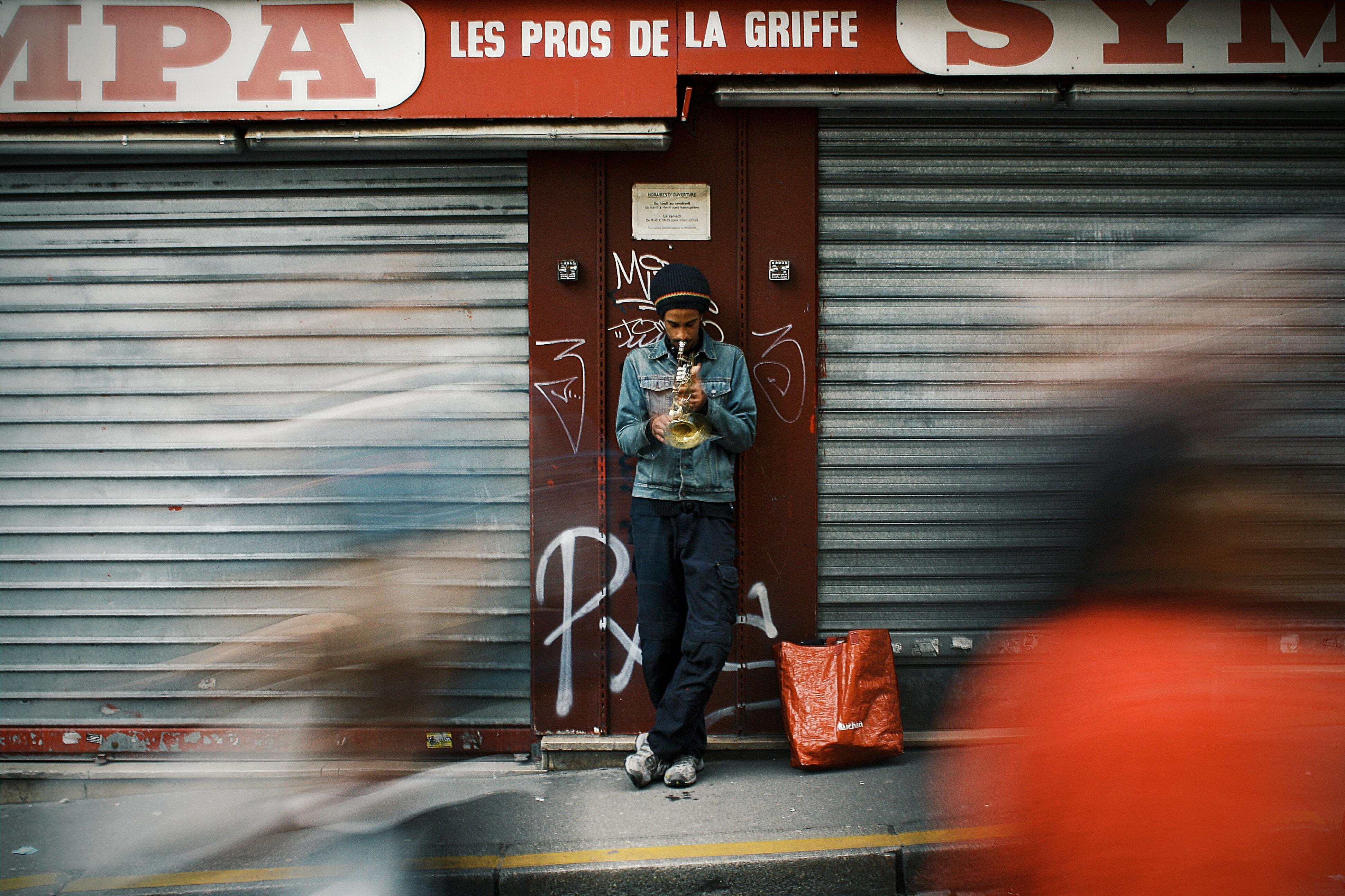 person wearing denim jacket standing near roller shutters