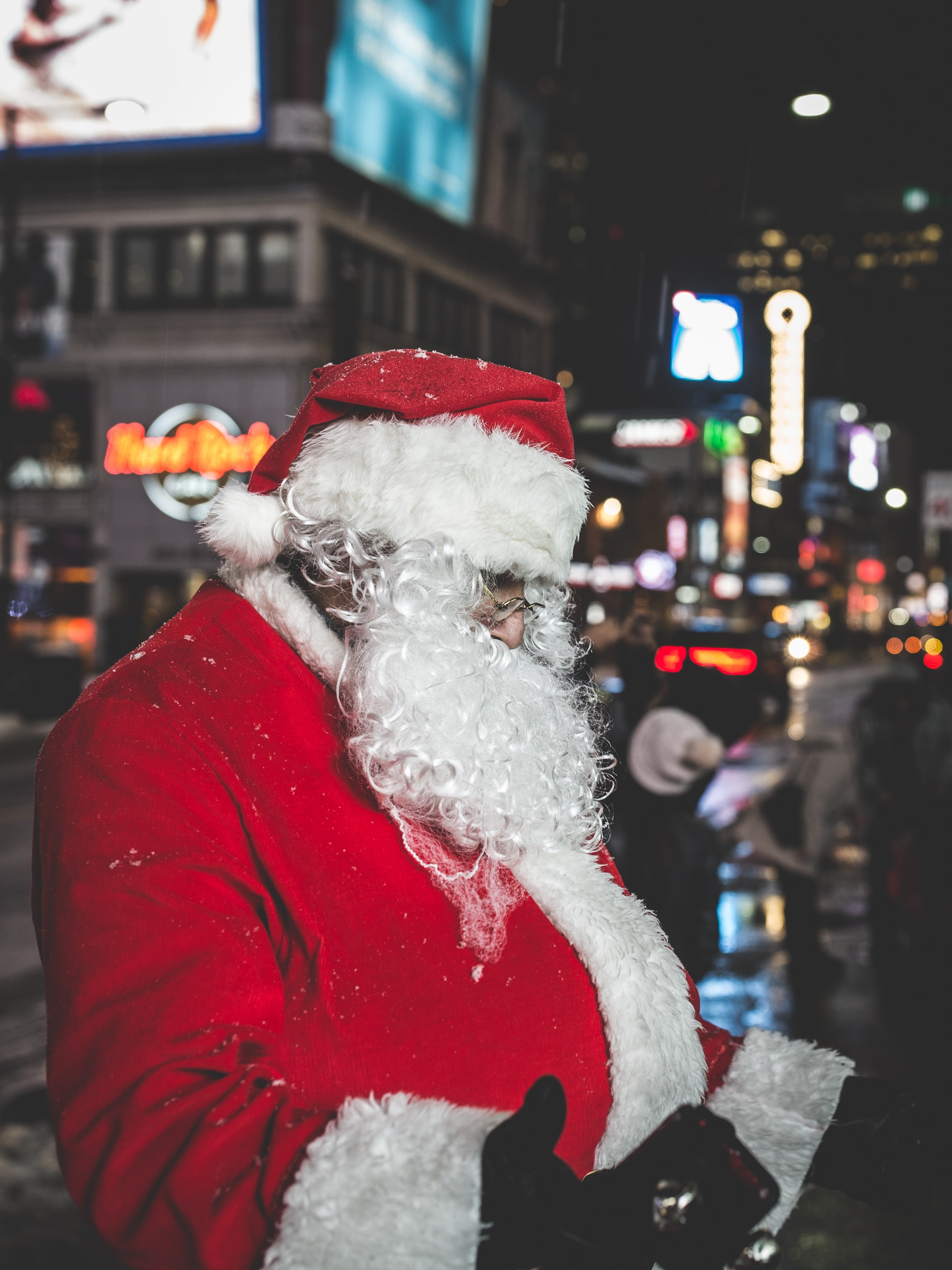 A man dressed as Father Christmas standing in the street at Dundas Square at night