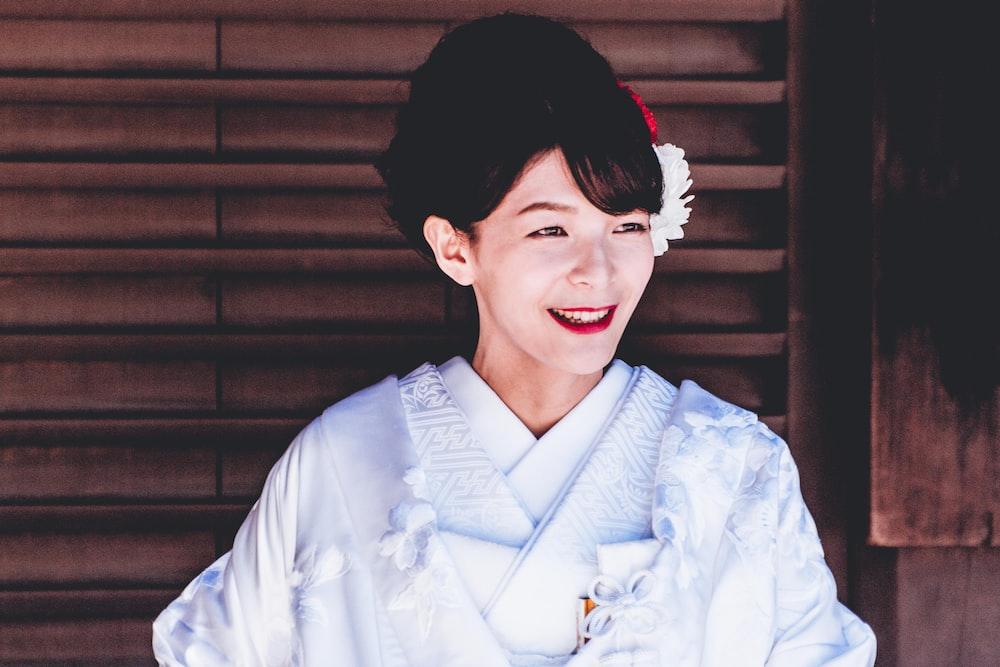 woman wearing white top near black window blinds in room