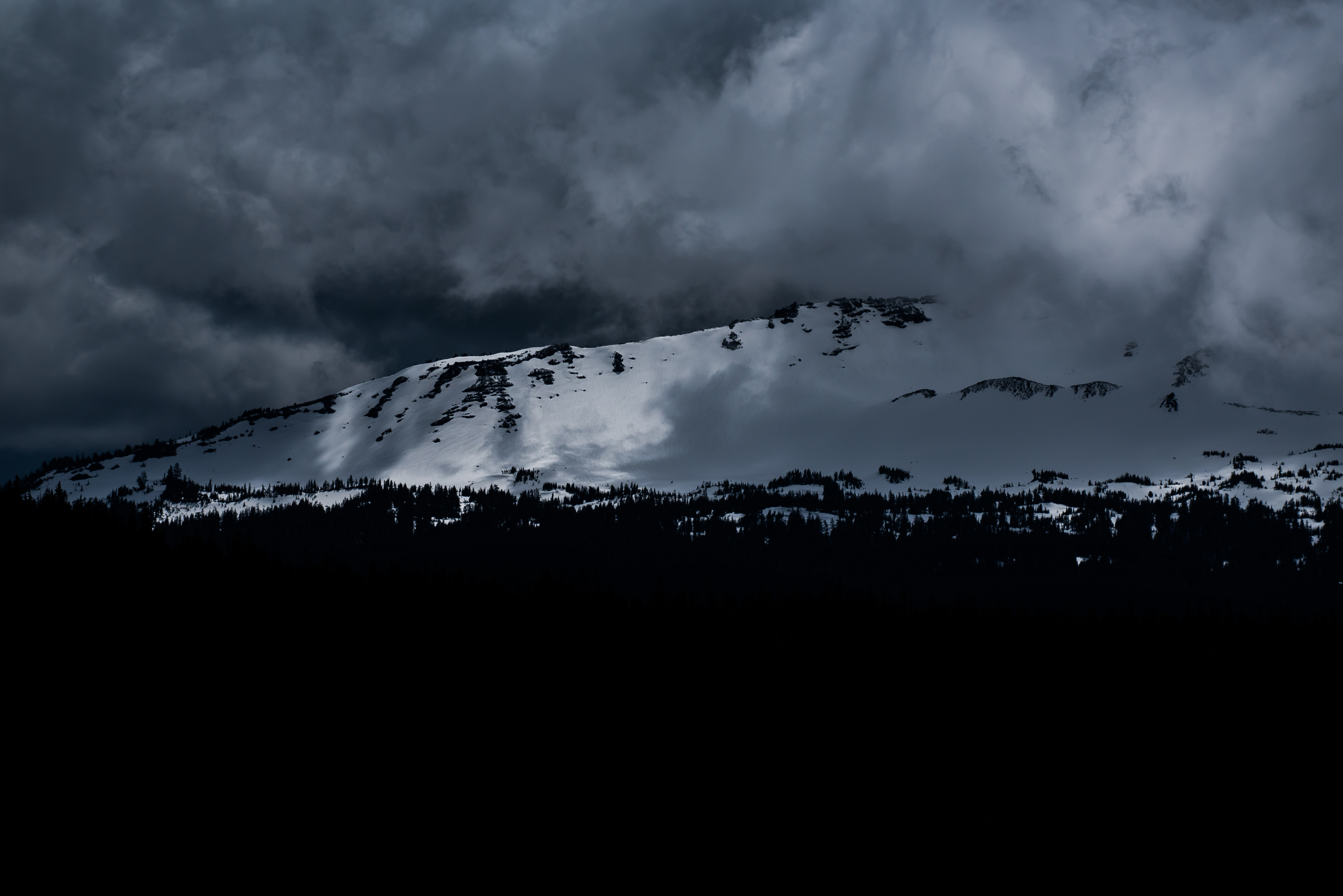 A mountain ridge with snow-covered slopes under an overcast sky in Silverthorne