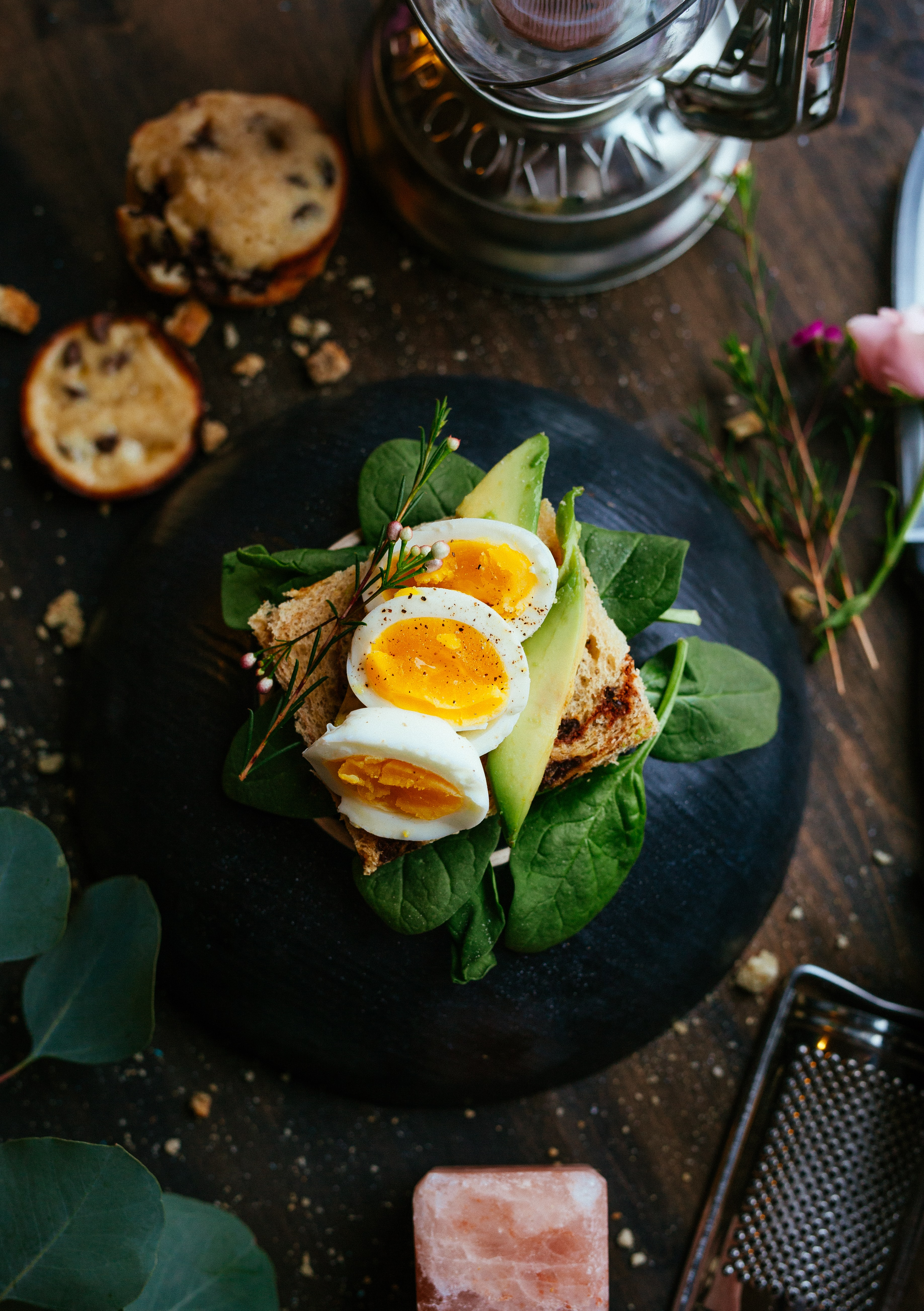 Avocado toast with egg and herbs on a rustic table