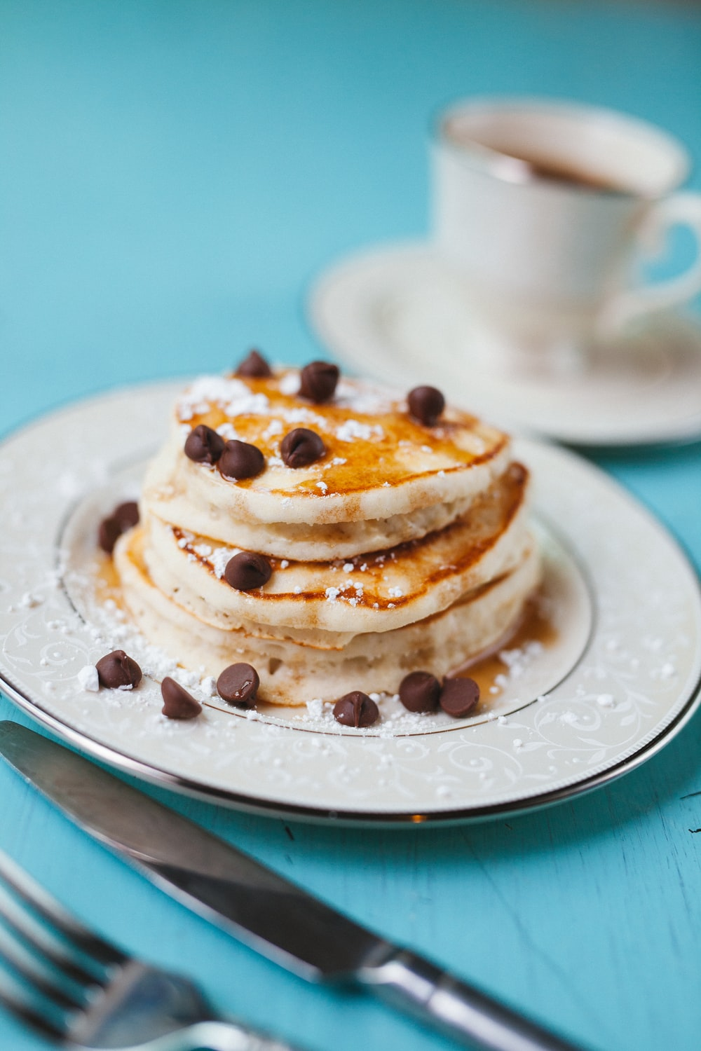 Chocolate chip covered pancakes on a plate.