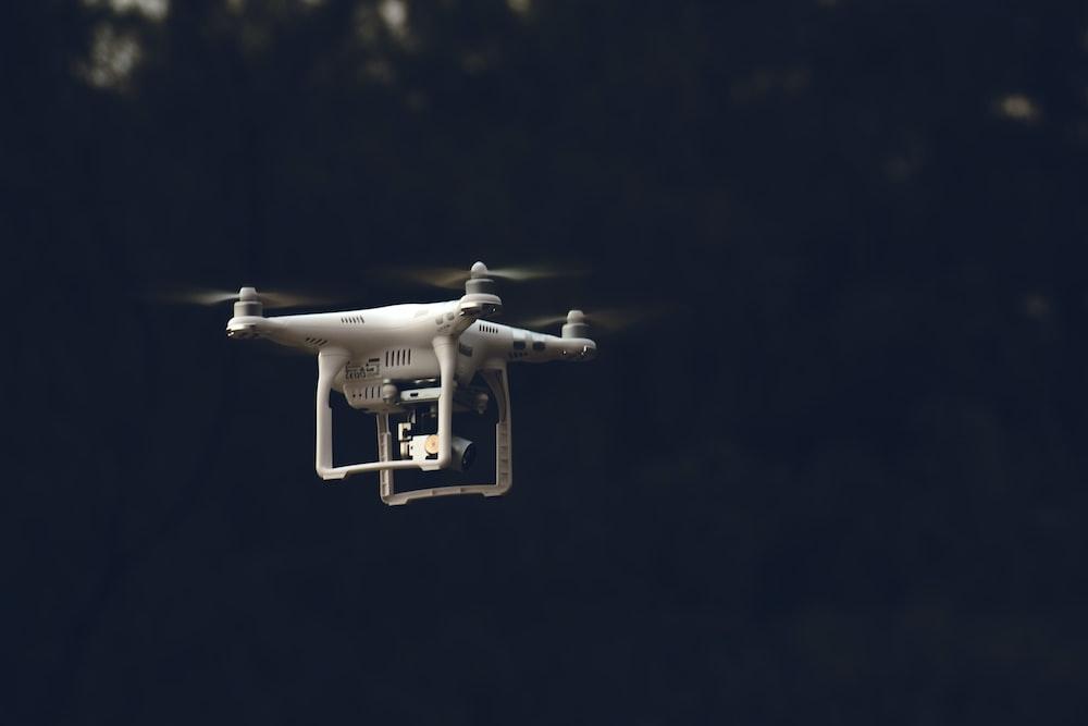 white DJI phantom-series quadcopter flying during daytime