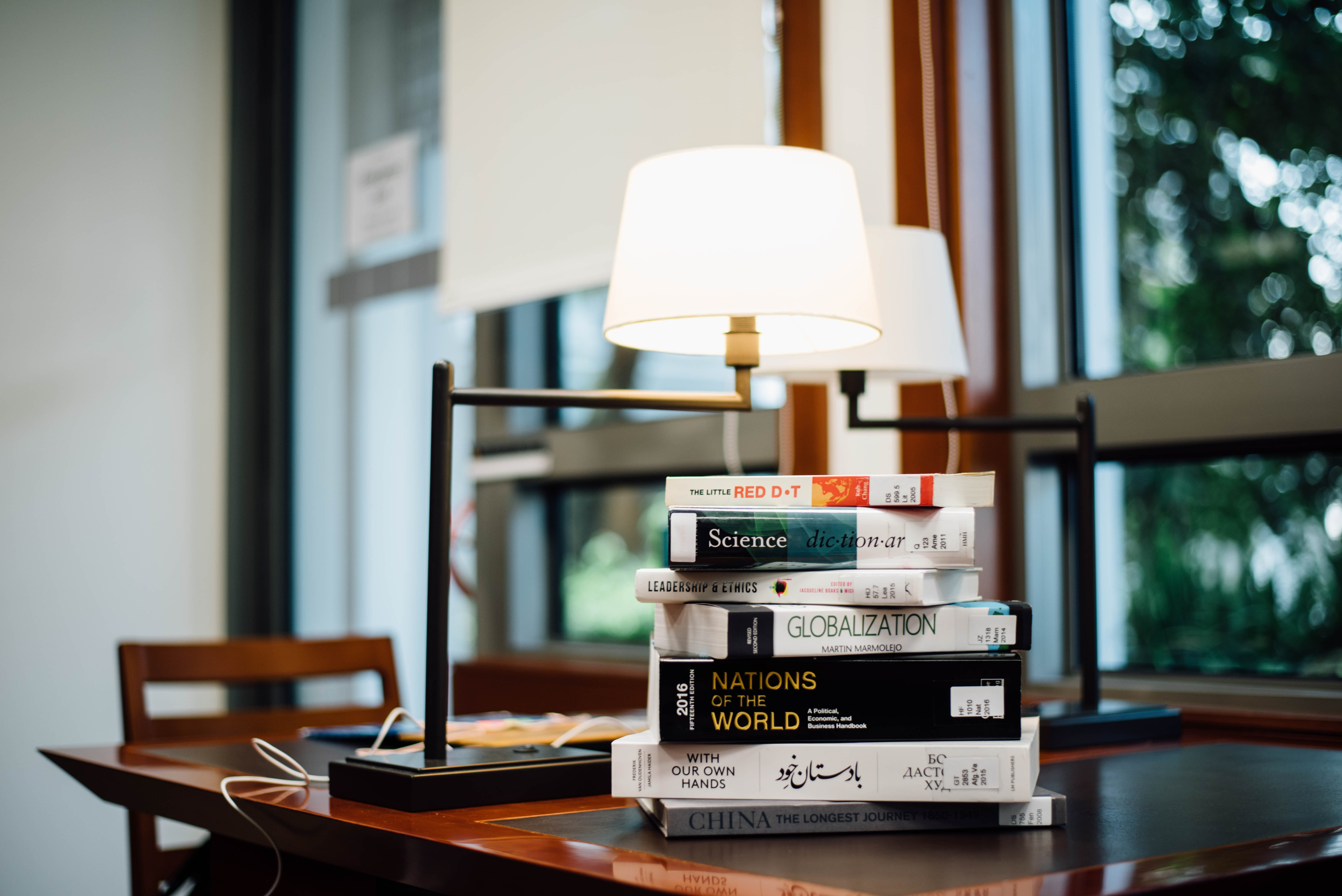 Interior with lamps on a wooden table and a stack of books near a window