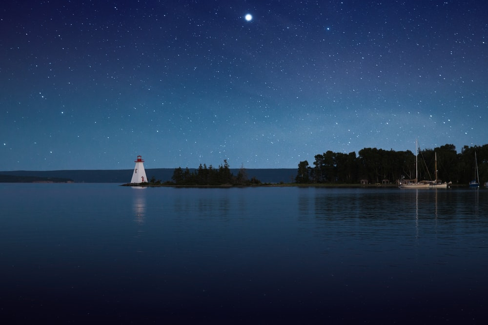 photograph of white lighthouse near calm body of water at night