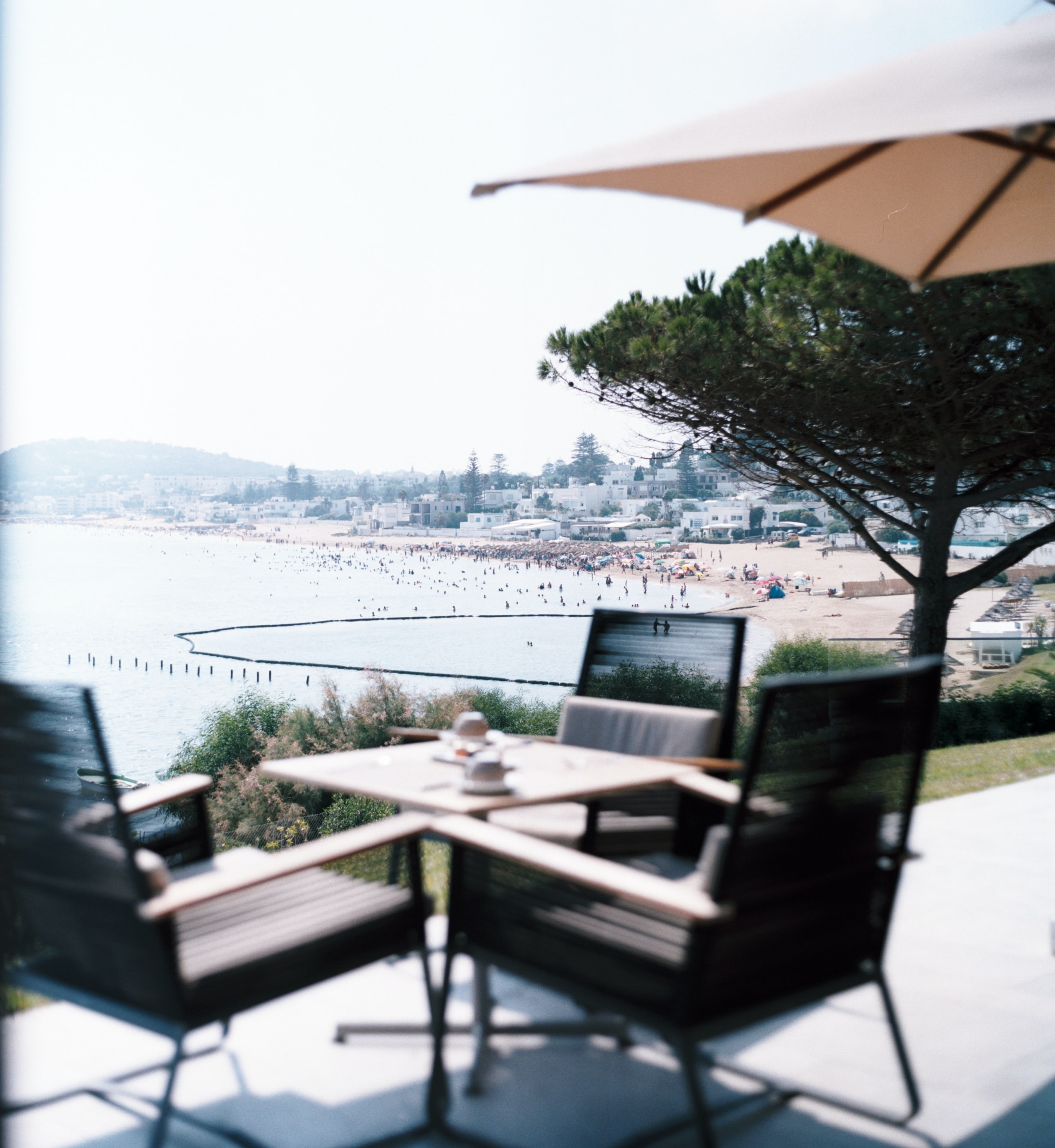 A patio with three chairs at a square table with a view on a crowded beach and a coastal town