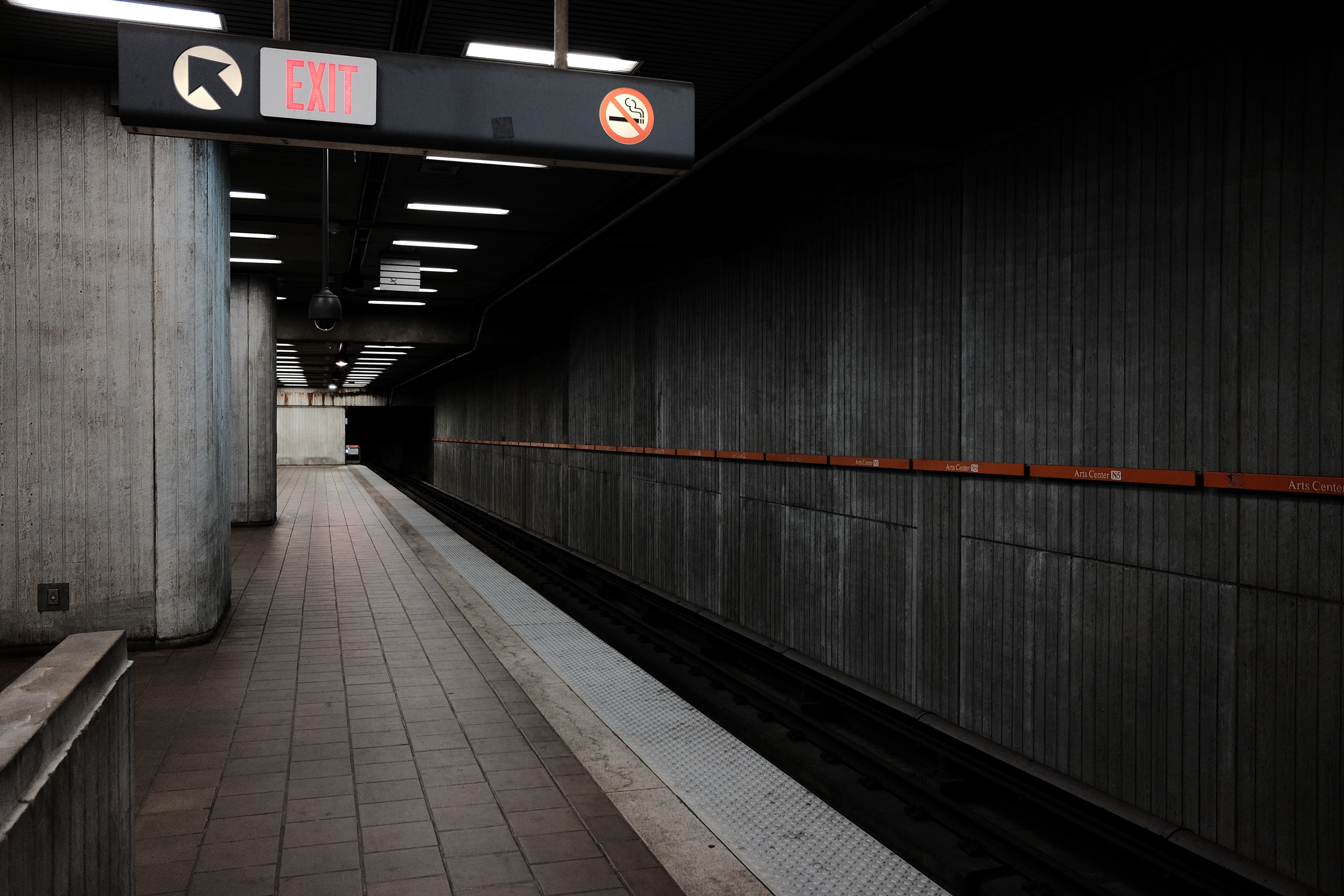 Subway platform with exit sign and concrete architecture and tunnel, Arts Center Transit Station