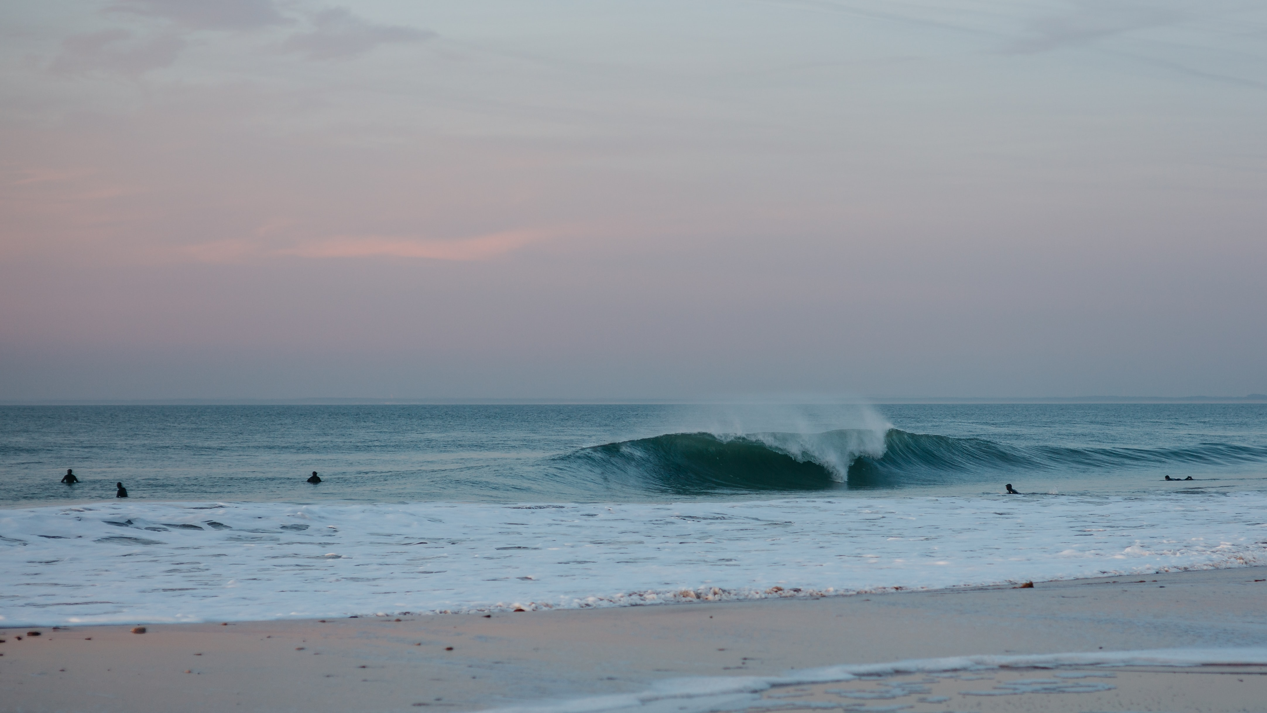 Ocean wave and people surfing at Plage du Petit Bec after sunset