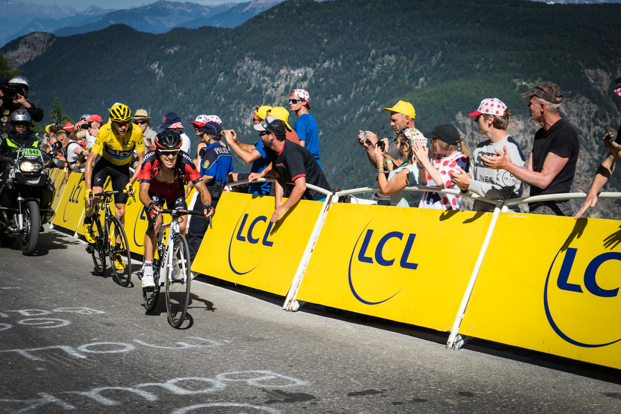 Cyclists and a dirt bike passing fans at the Tour de France race in France