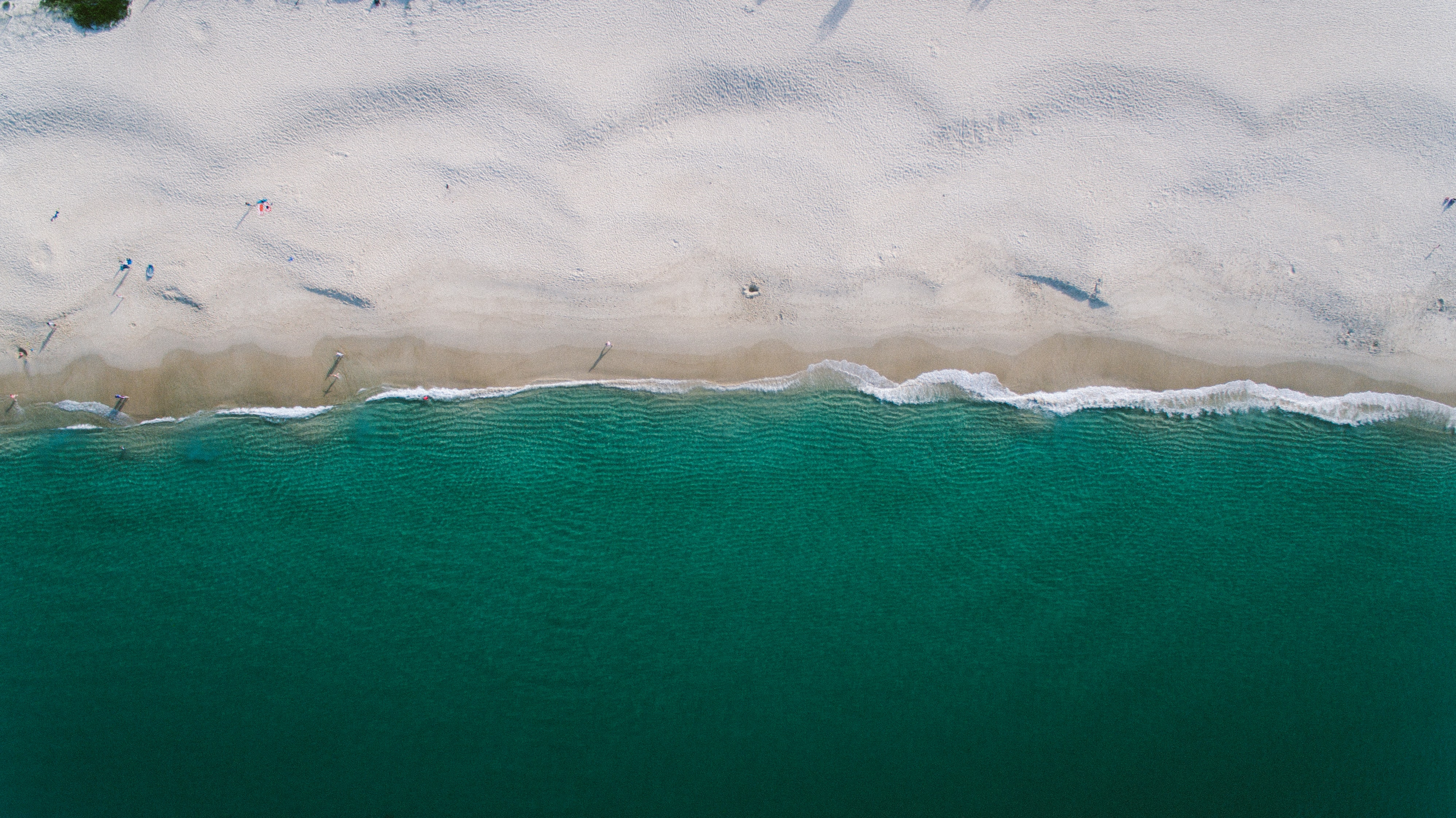 Drone aerial view of a sand beach by the ocean at Nelson Bay