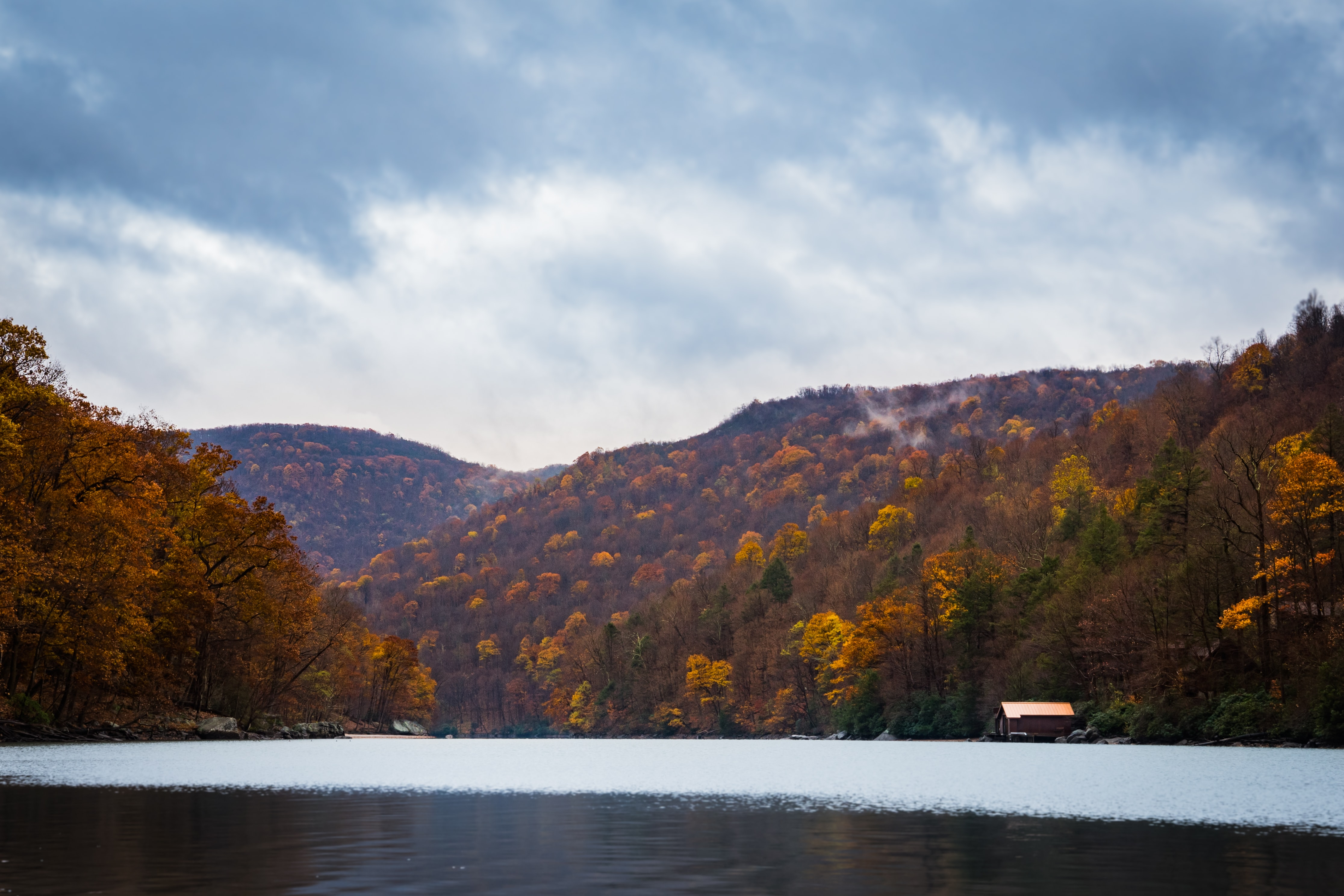 The half-frozen Cheat Lake with a boathouse and orange-leaved trees on its shore