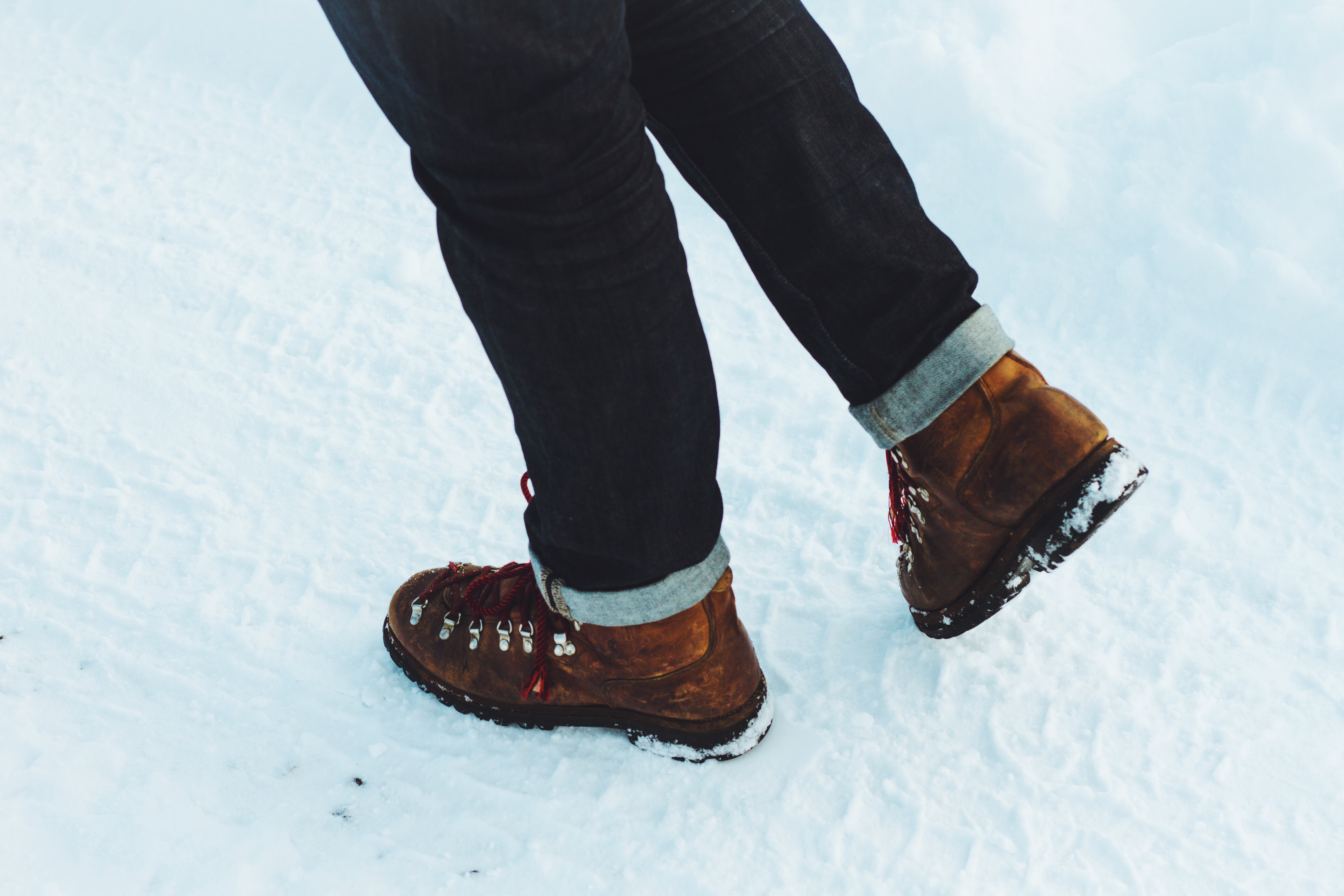 Brown winter fashion boots walking on snow