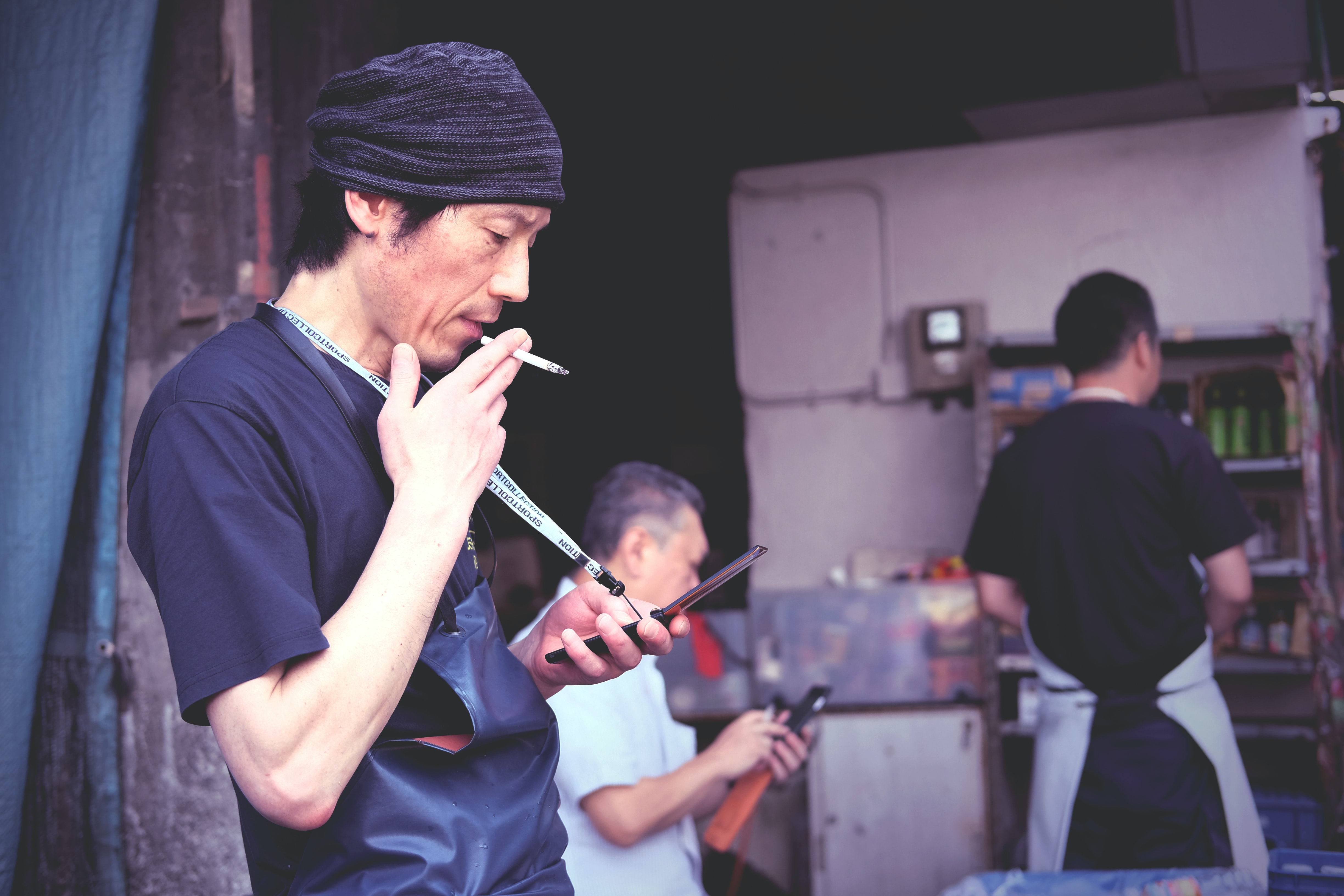 A man is smoking and looking at his phone in the foreground at Tsukiji Market.