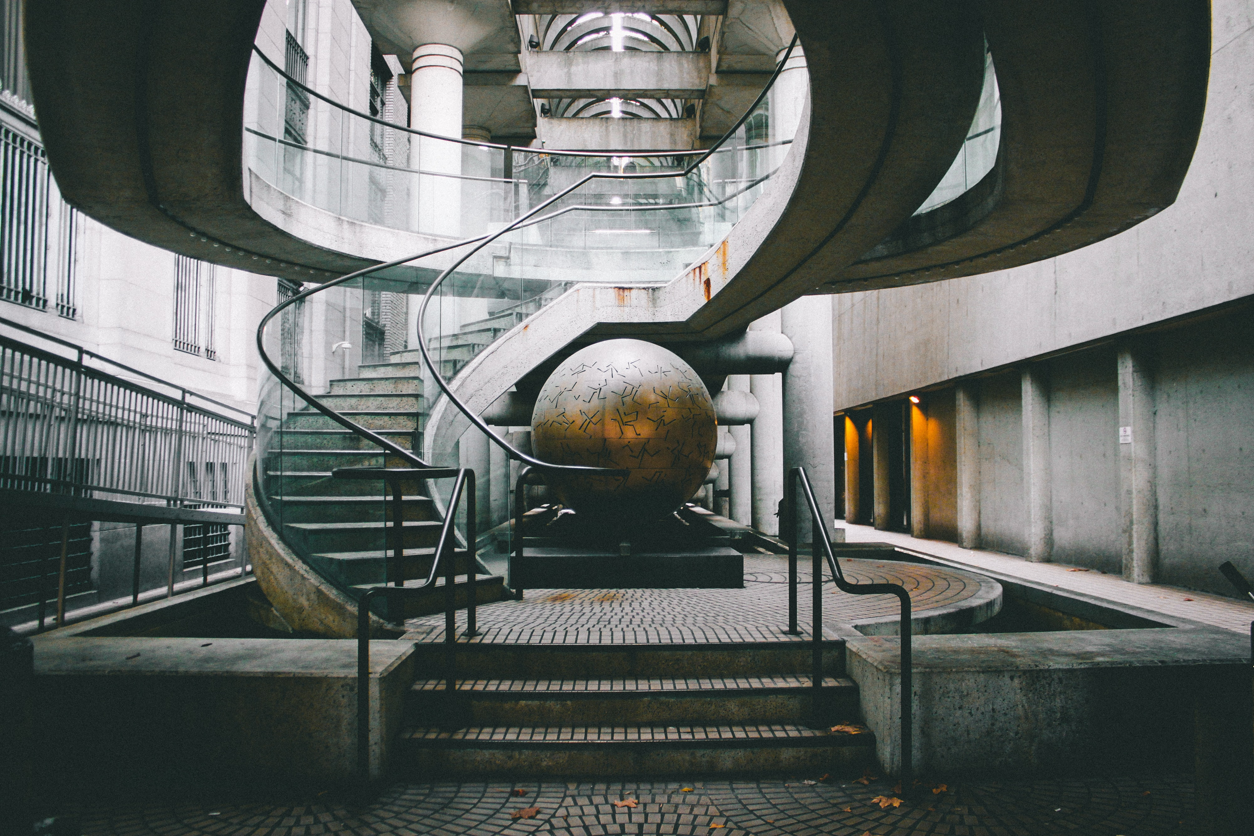 landscape photography of grey staircase with globe under