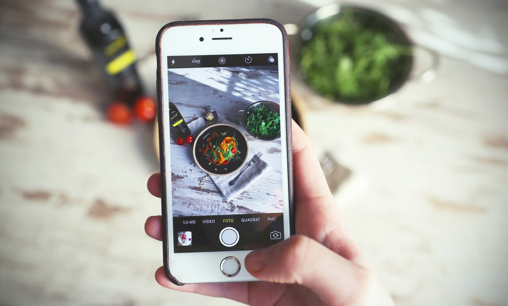 Person taking an Instagram photo on an iPhone of their food