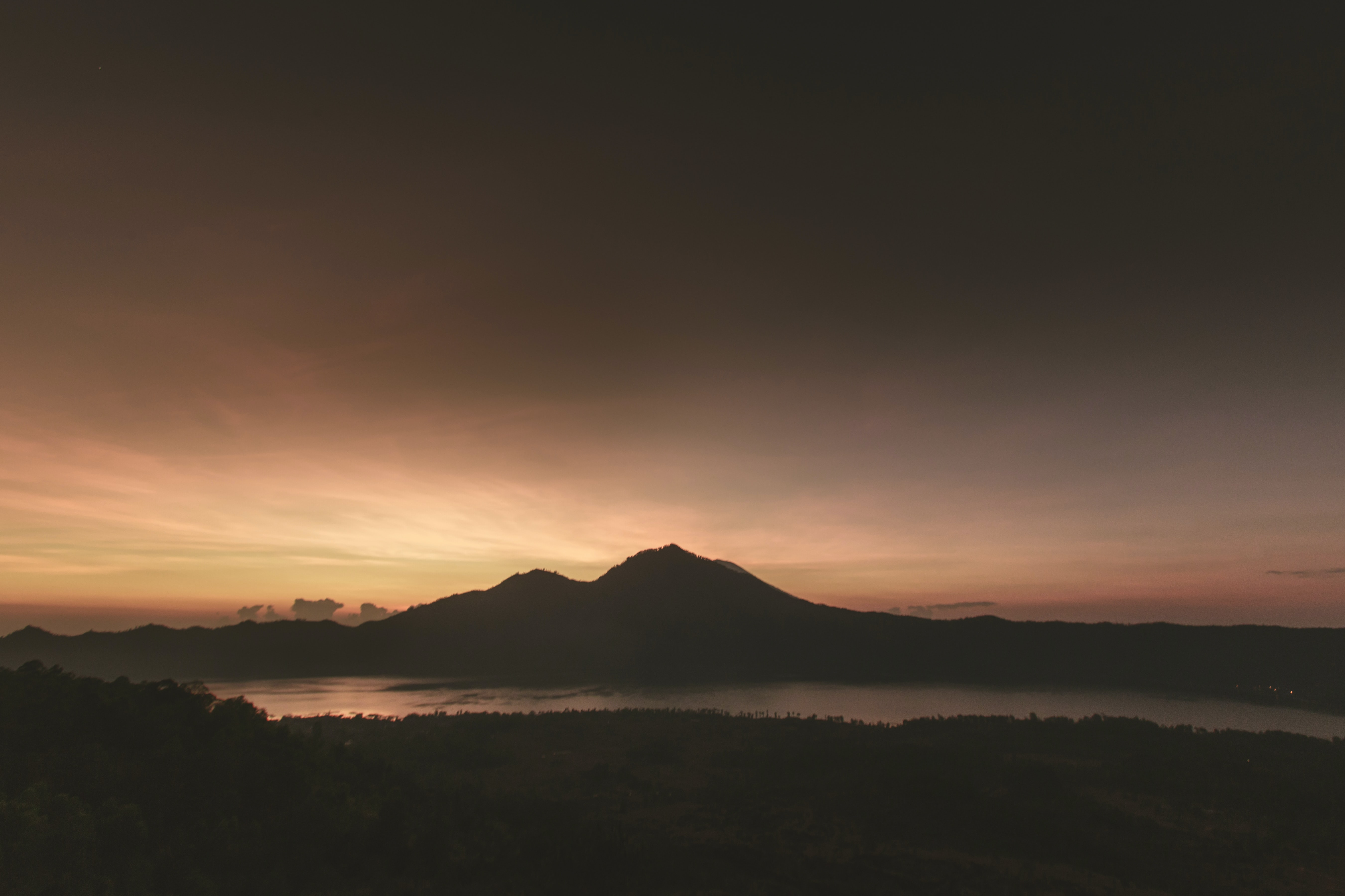 silhouette of mountain near body of water under brown clouds