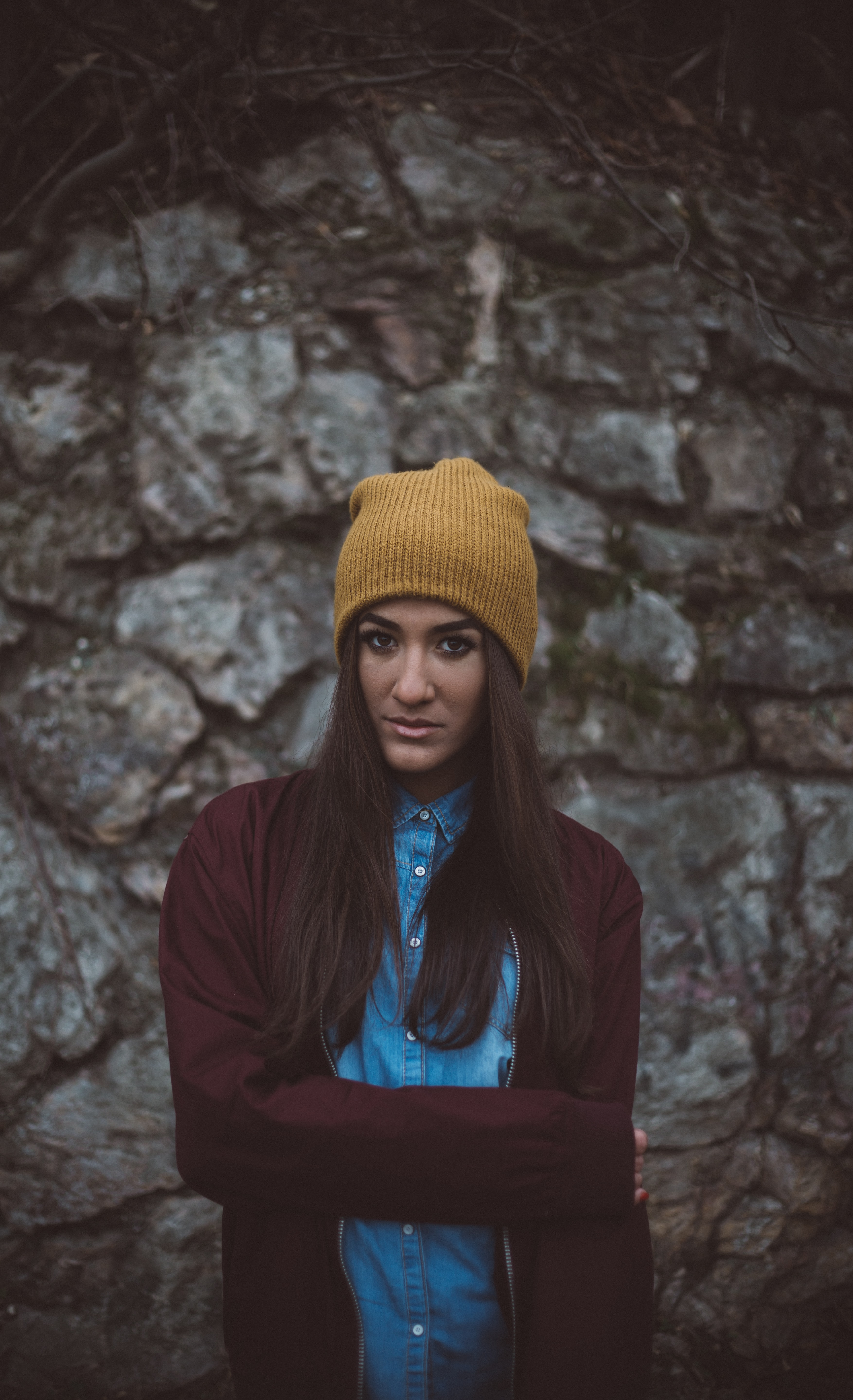 A woman in a brown beanie and maroon jacket against a stone wall in Hungary.