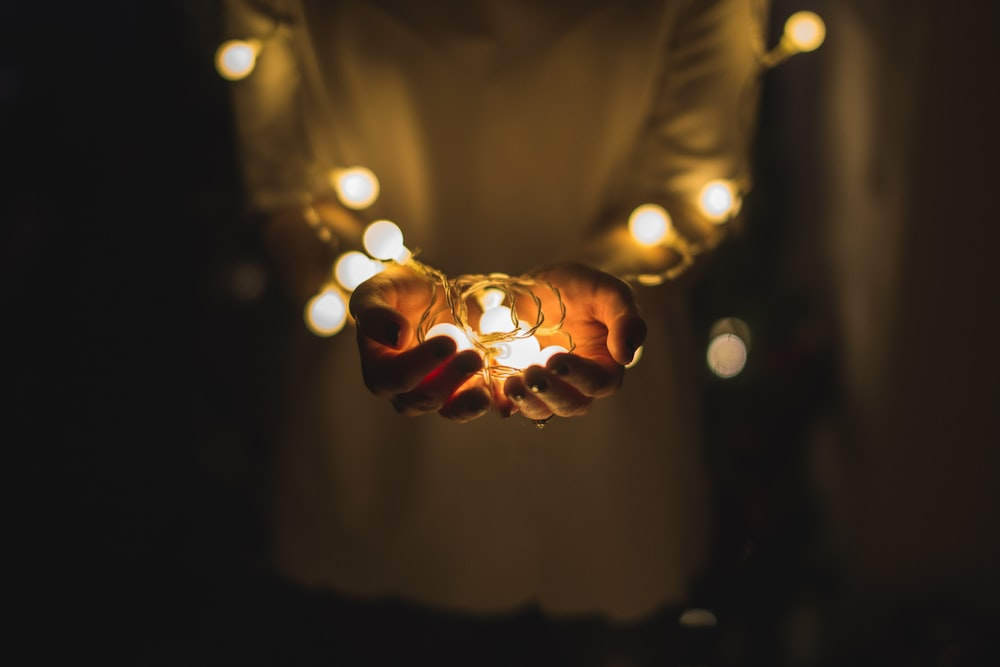 person holding string lights