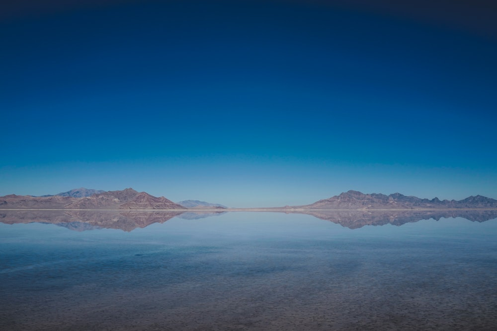 body of water and mountains during daytime