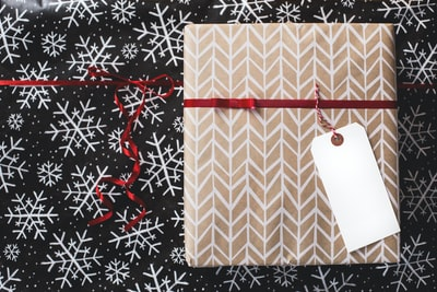 gold and white gift box on white and black fair-isle print surface wrapping paper teams background